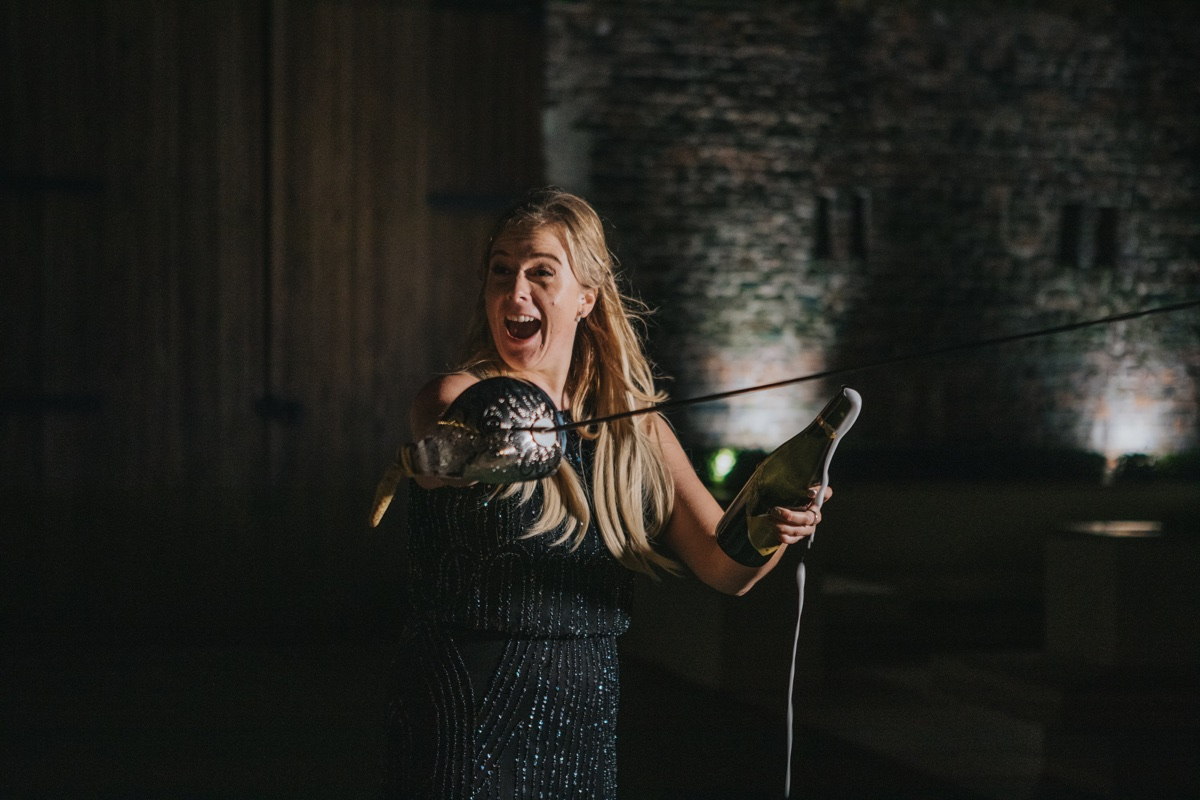 Woman wielding sword opens bottle of champagne.  Nothing to see here. Photo by Bloom Weddings
