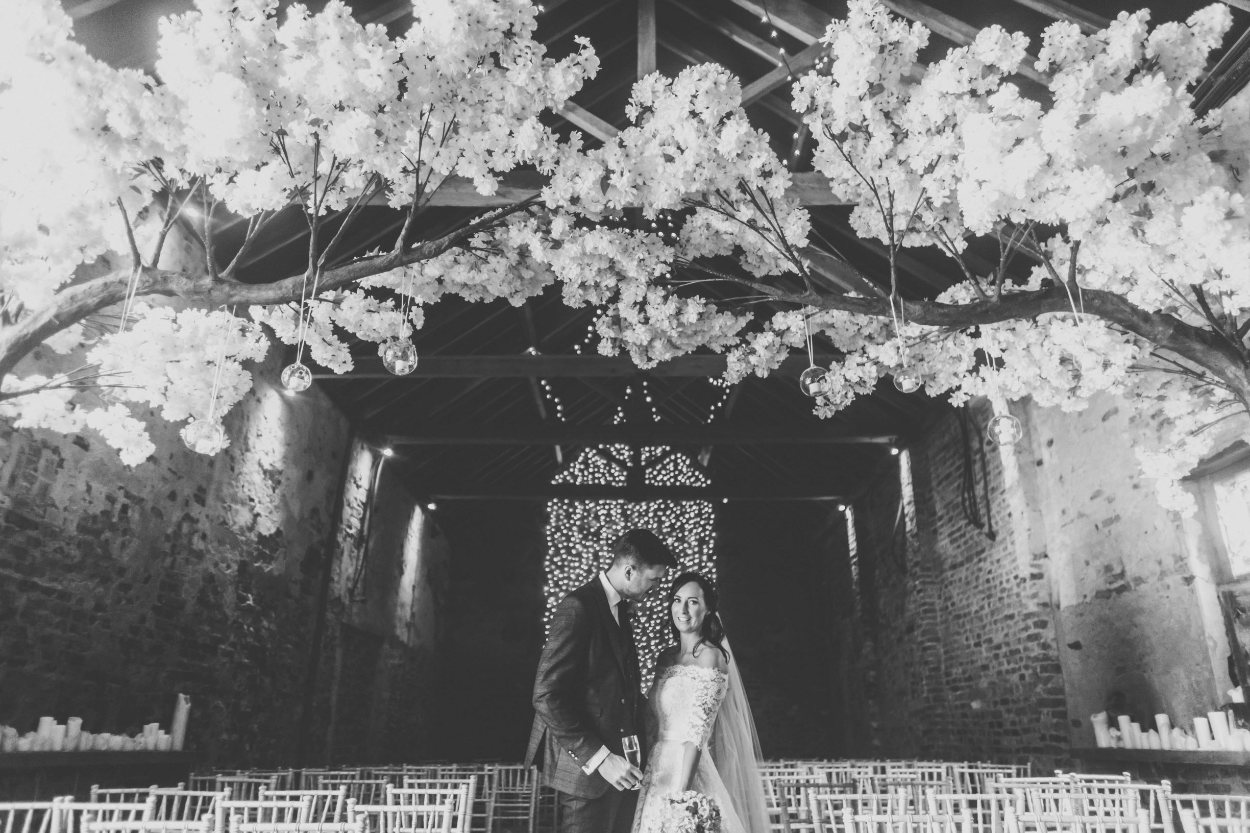 Krista and Daniel take a moment amid the blossom and lights of The Normans Ceremony Barn.jpg