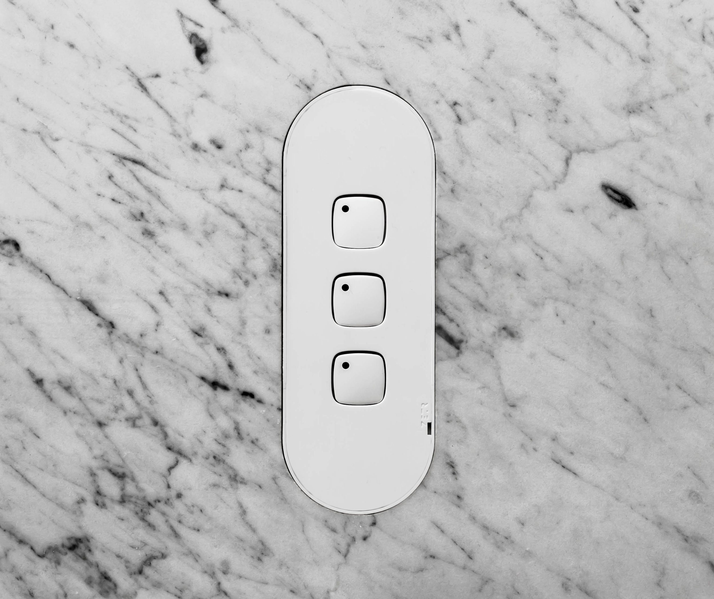 ZETR three gang switch in matte white with adjustable mounting assembly finished in marble.