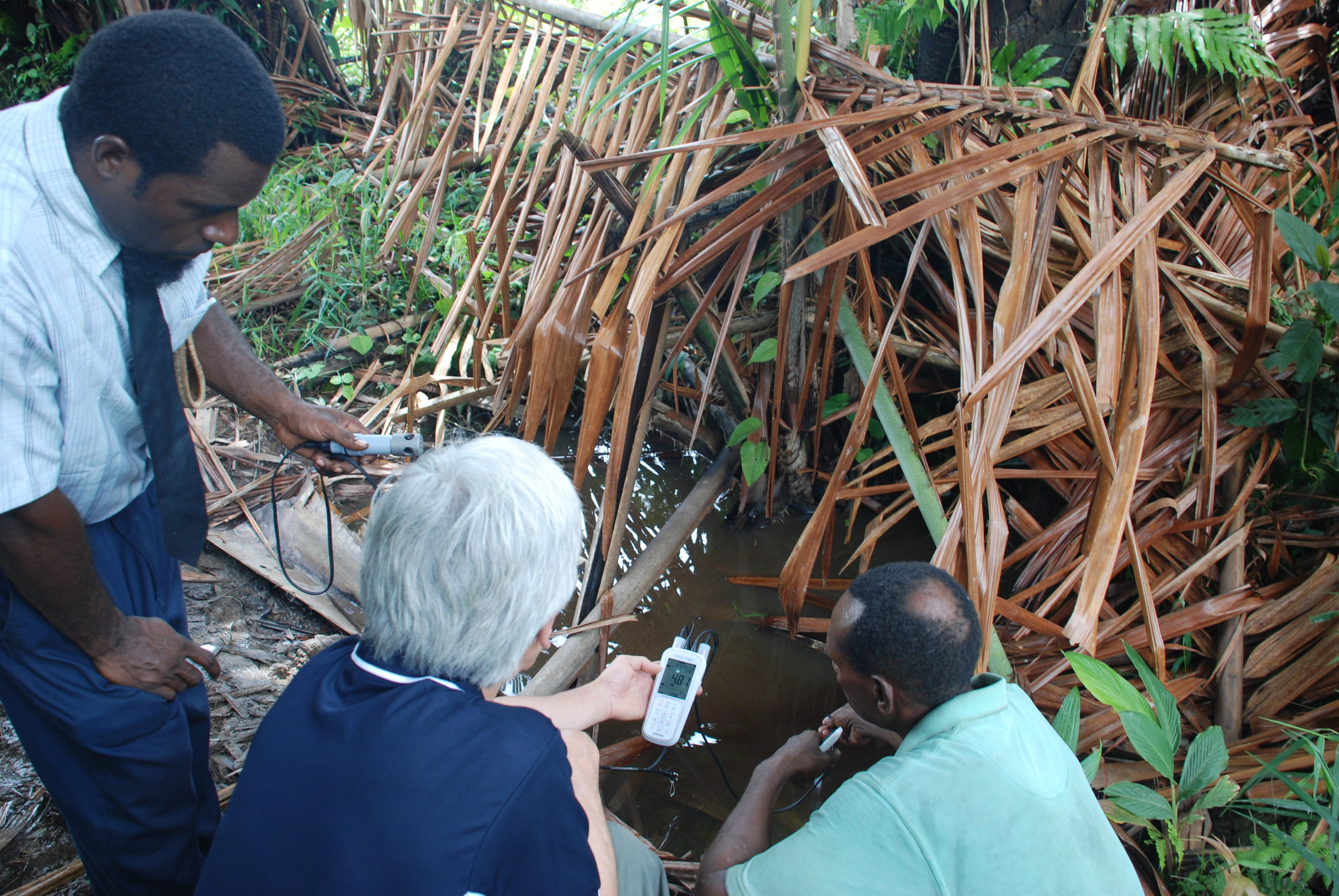 Together with the local villagers, Martin tests the water quality of the bush well.    PHOTO: Madeleine Brezger