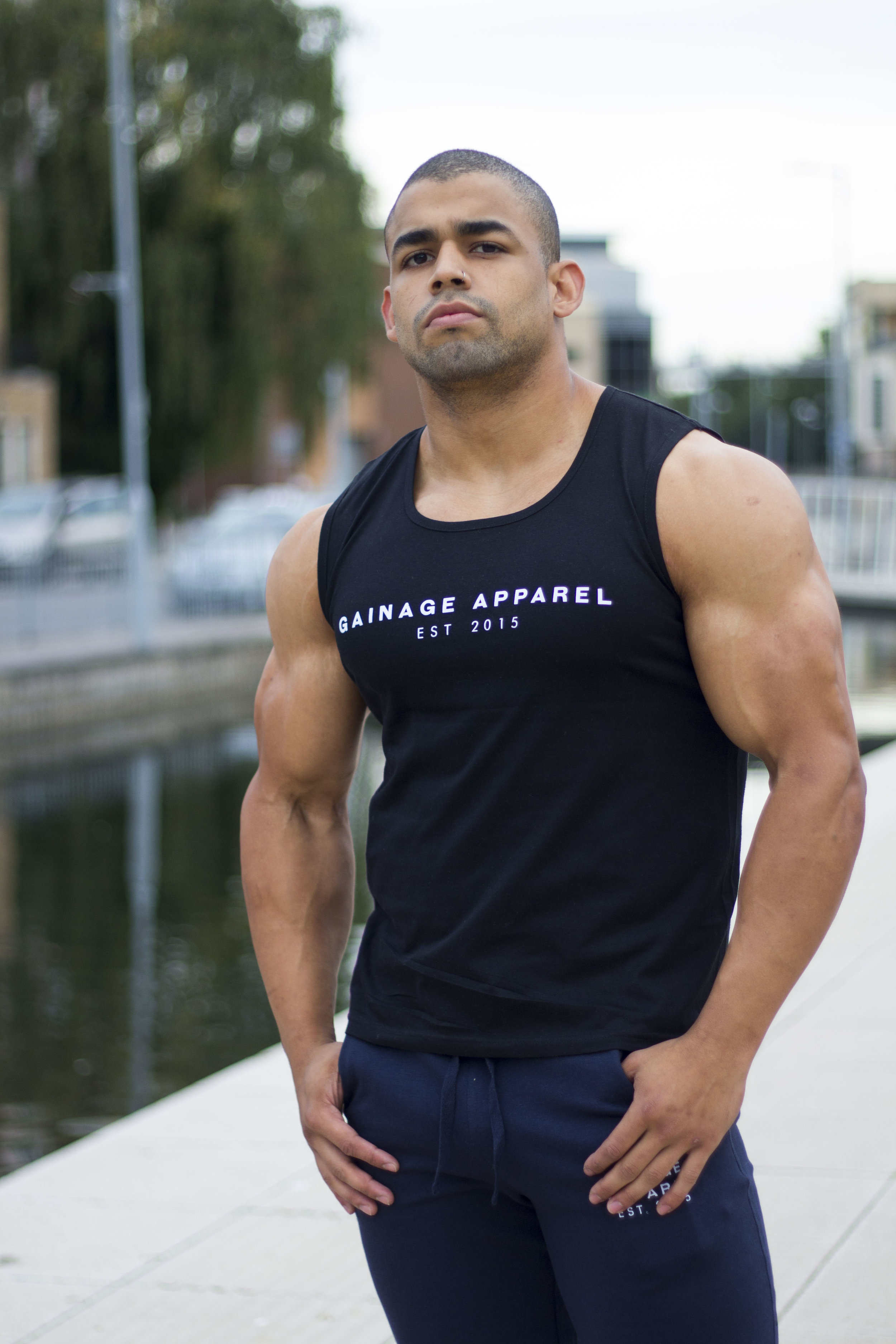 Fitness Enthusiast Daniel Gomez donning GAINAGE, the  black EST 2015 Vest  and  Navy Champ Tracksuit joggers