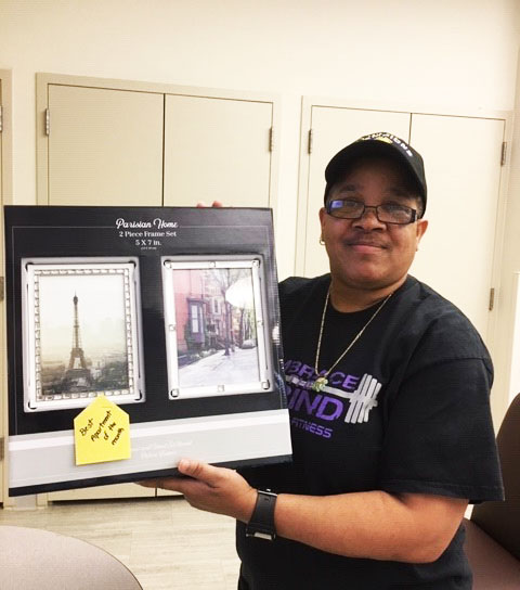 Andrea holding a donated picture frame that now hangs in her apartment.