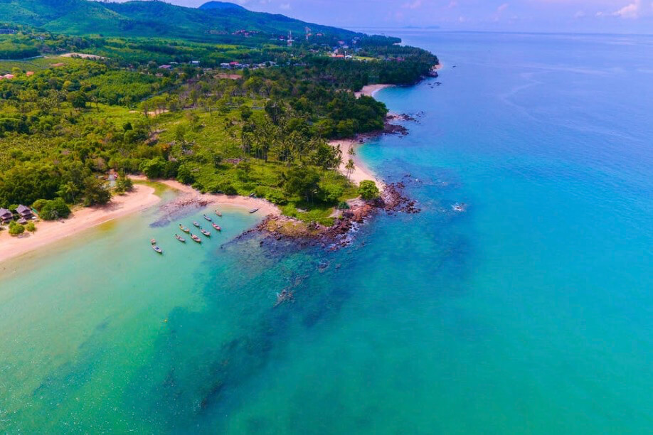 aerial view of beach with green forest and turquoise water
