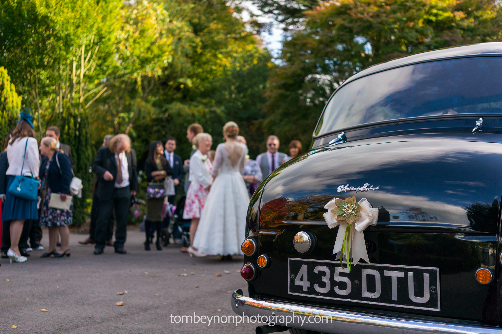The wedding car in the driveway of Rodbaston Hall as guests chat in the background