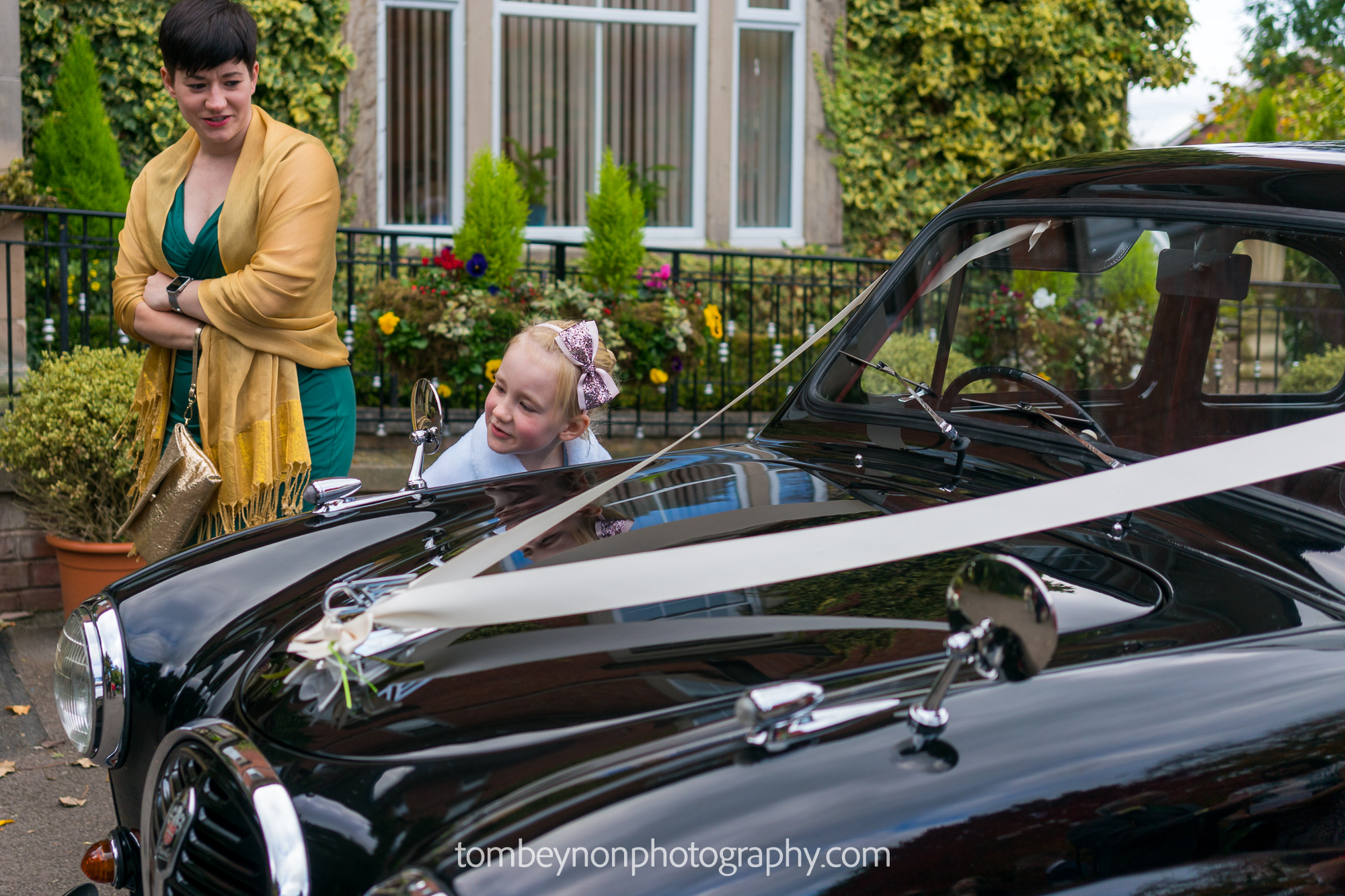 Small girl looks at her reflection in the mirror of the wedding car