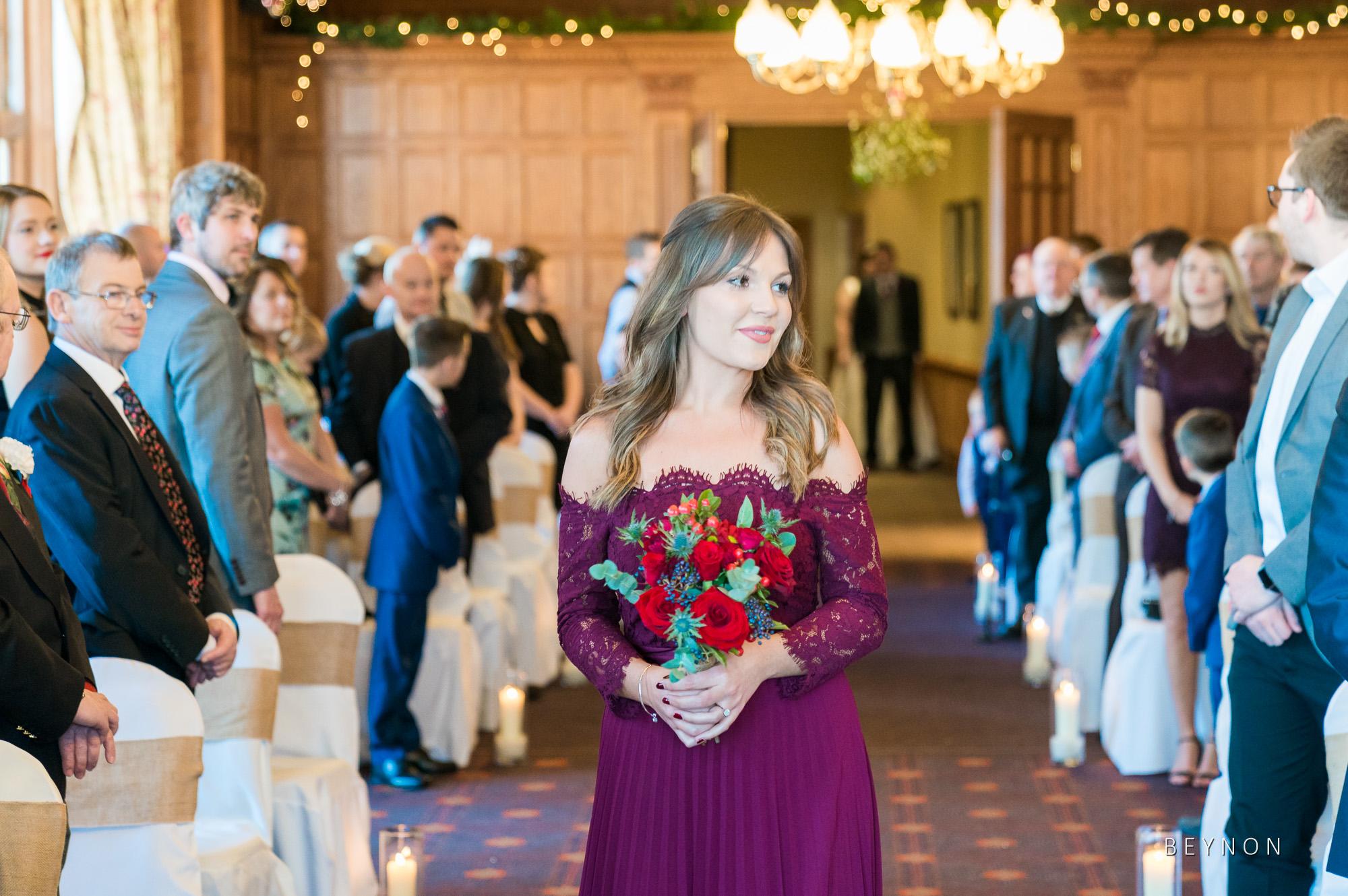 A bridesmaid walks down the aisle