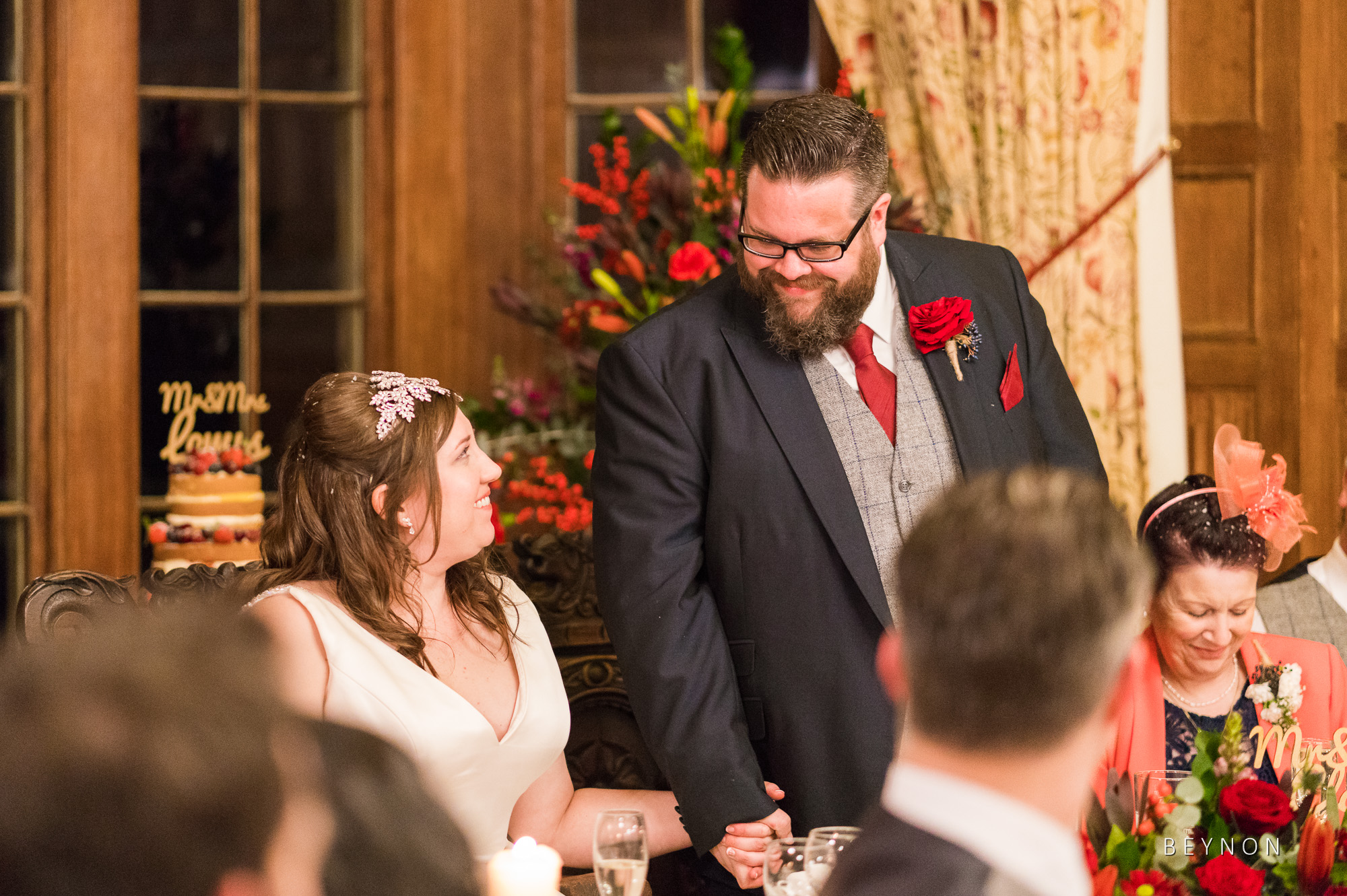 The Bride and Groom hold hands during his speech