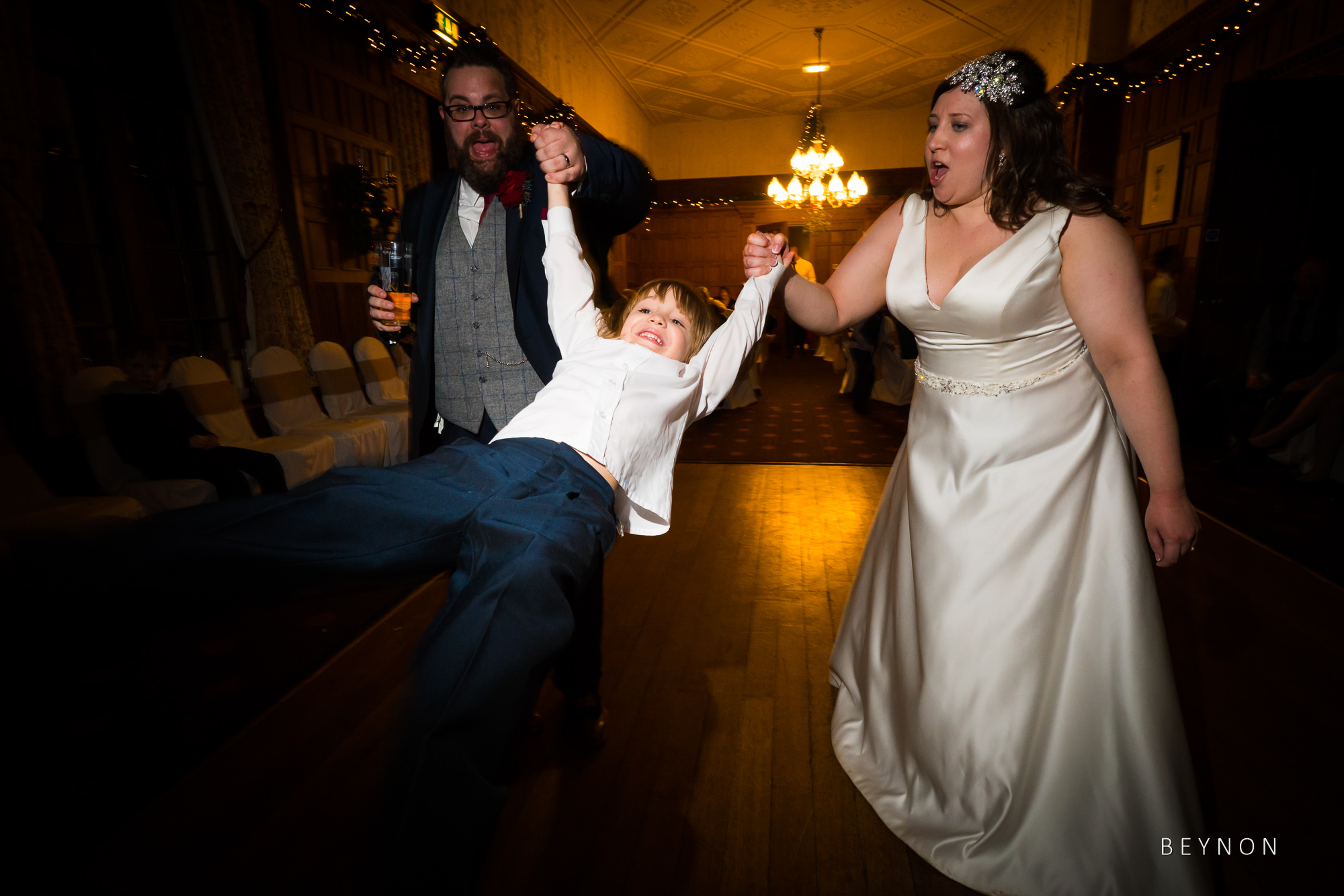 The Bride and groom dance with a small child