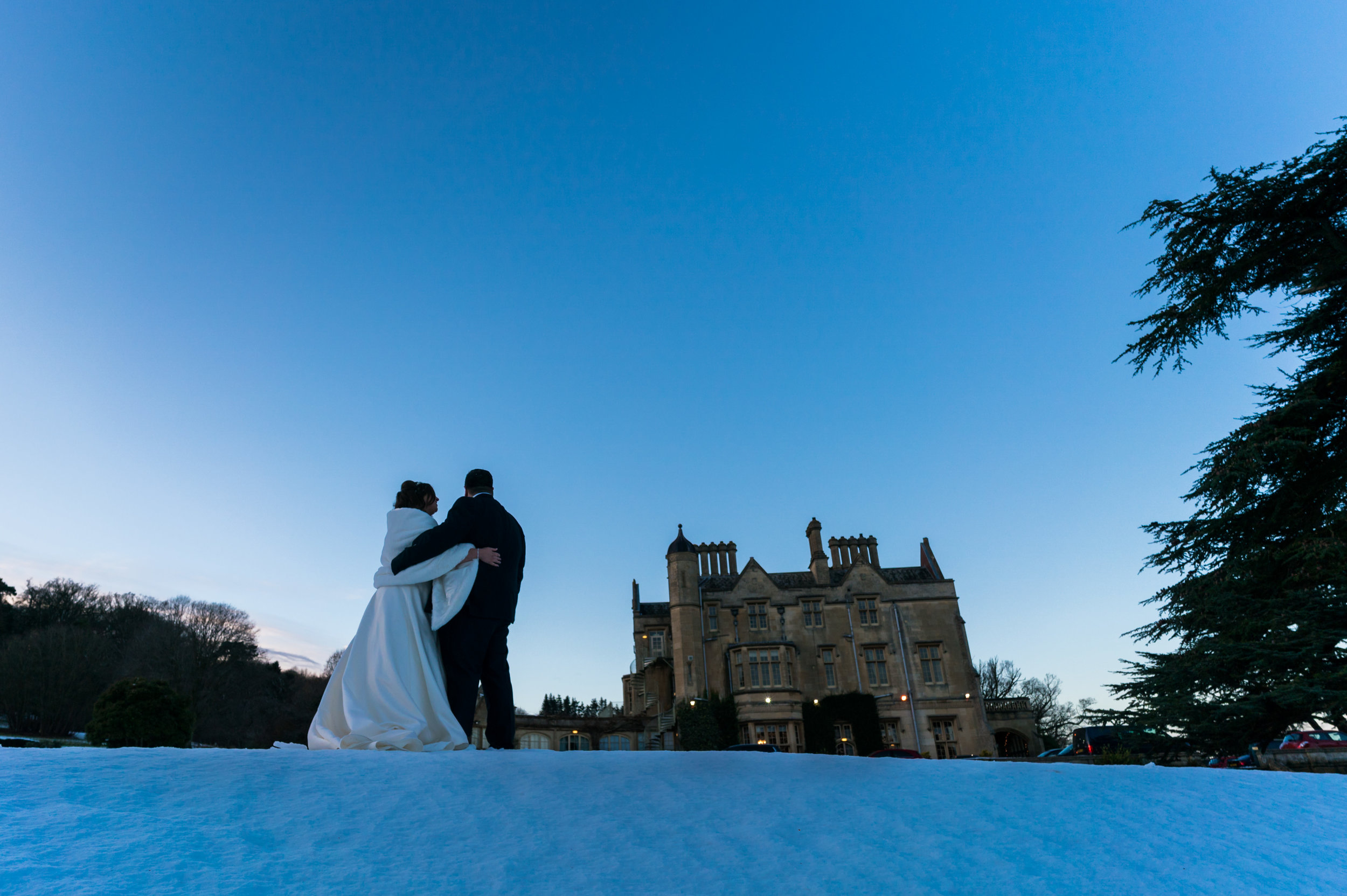 Dumbleton Hall in the snow and the happy couple link arms