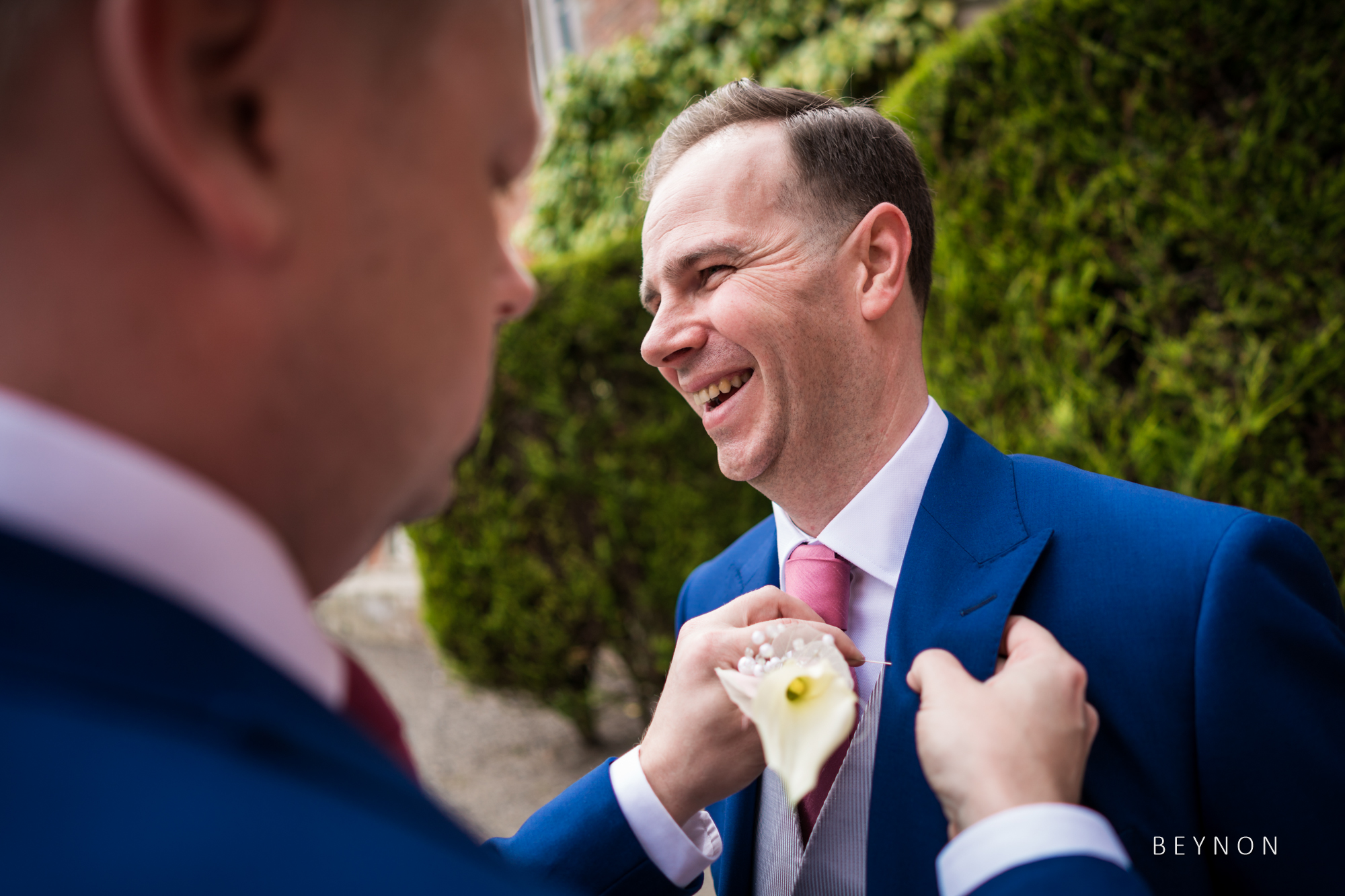 The groom has his buttonhole fix in place