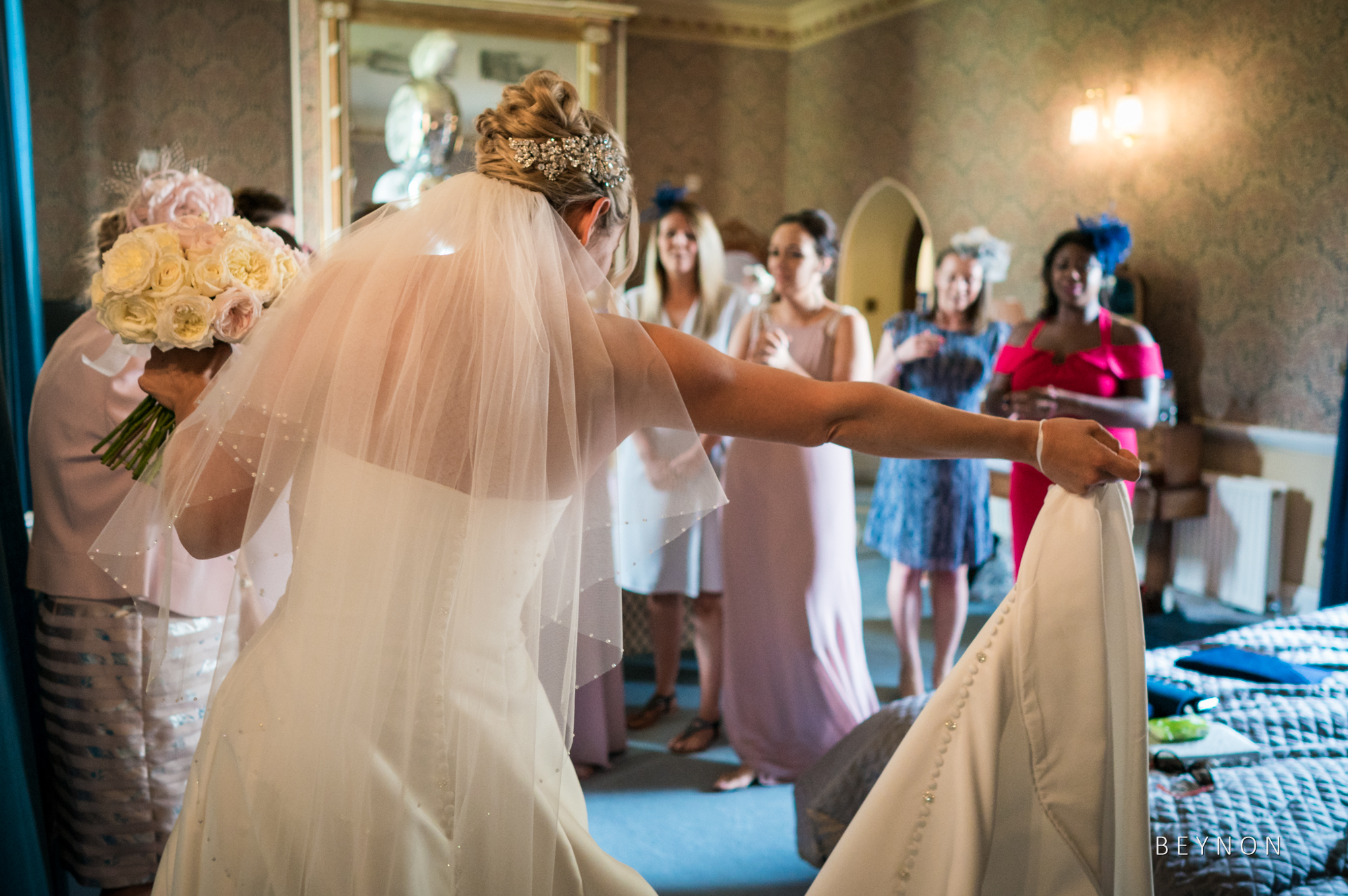 The bride shows of the dress to her bridesmaids