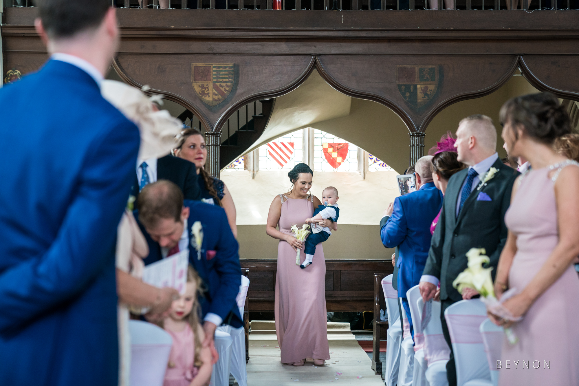 Bridesmaid walks down the aisle with the pagepoy