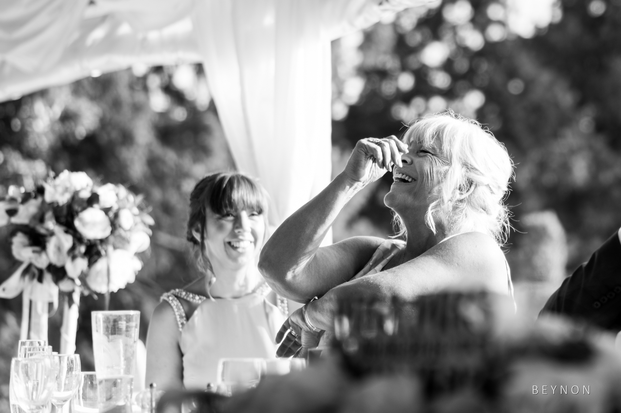 The mother of the bride laughs during the speeches
