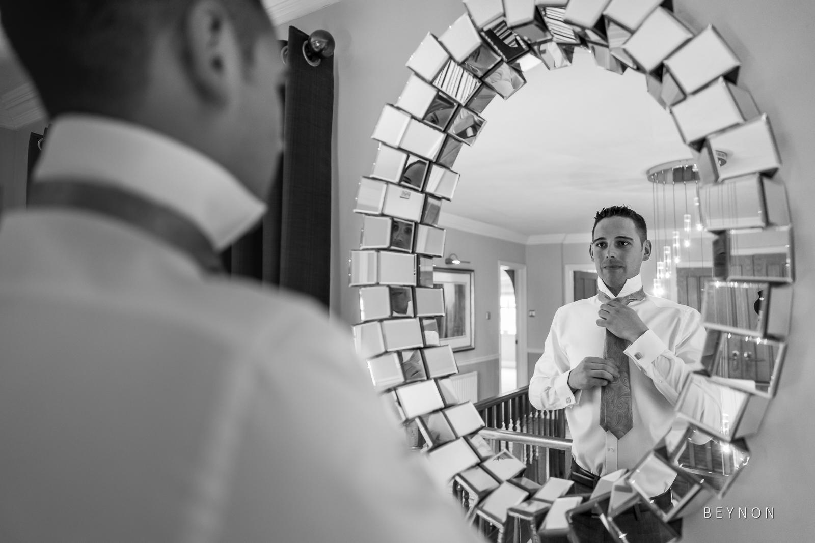 The brides brother ties his tie