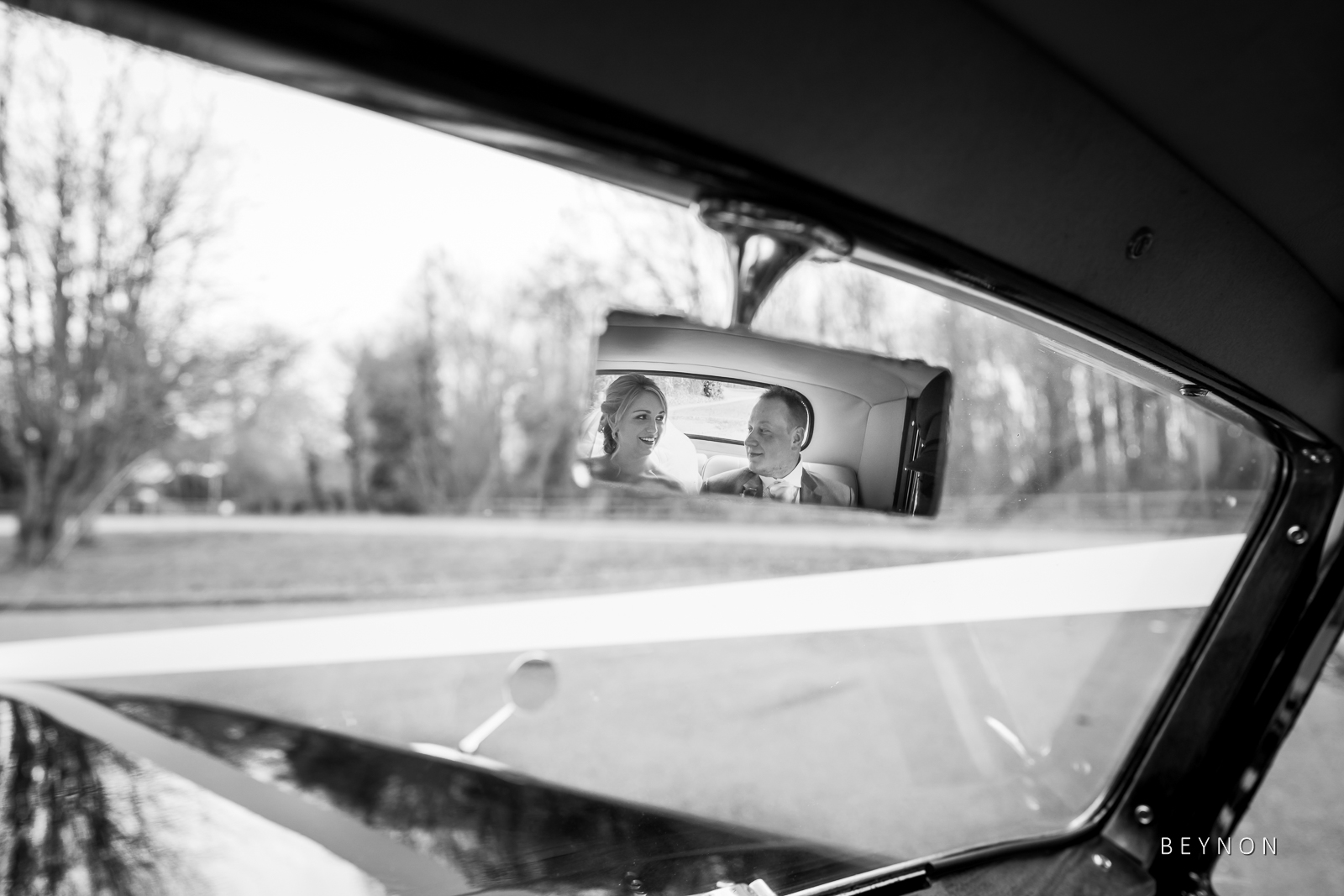 Photograph of Bride and Groom in rear view mirror