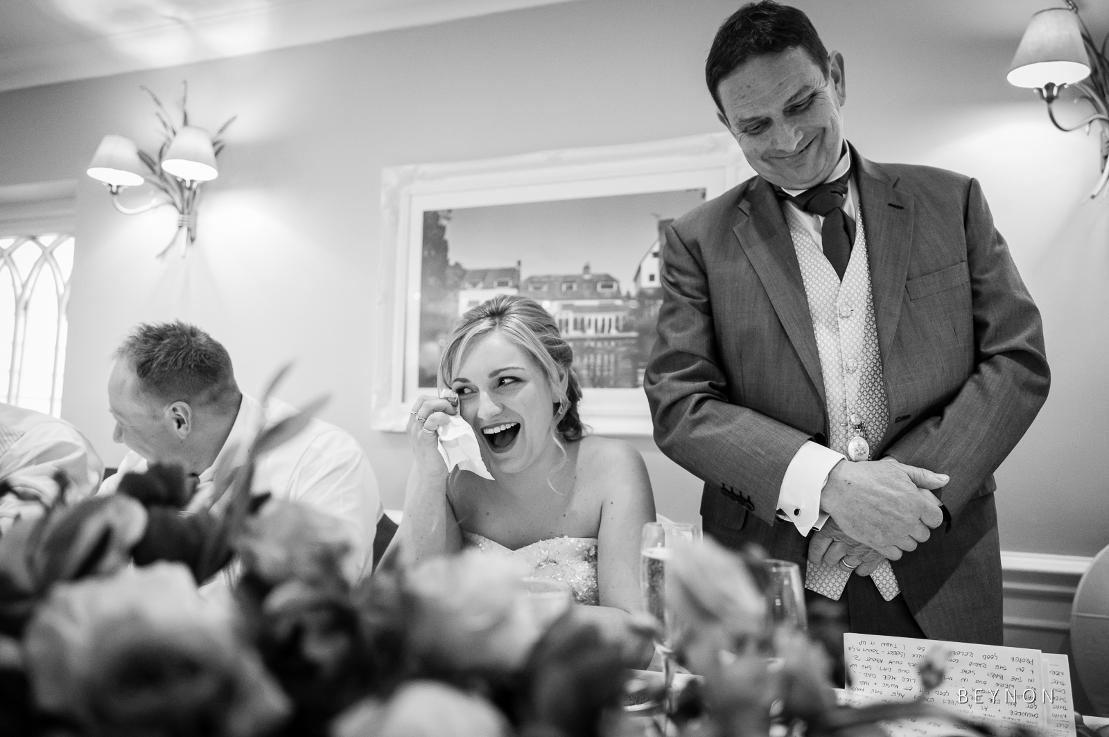 The bride laughs during speech