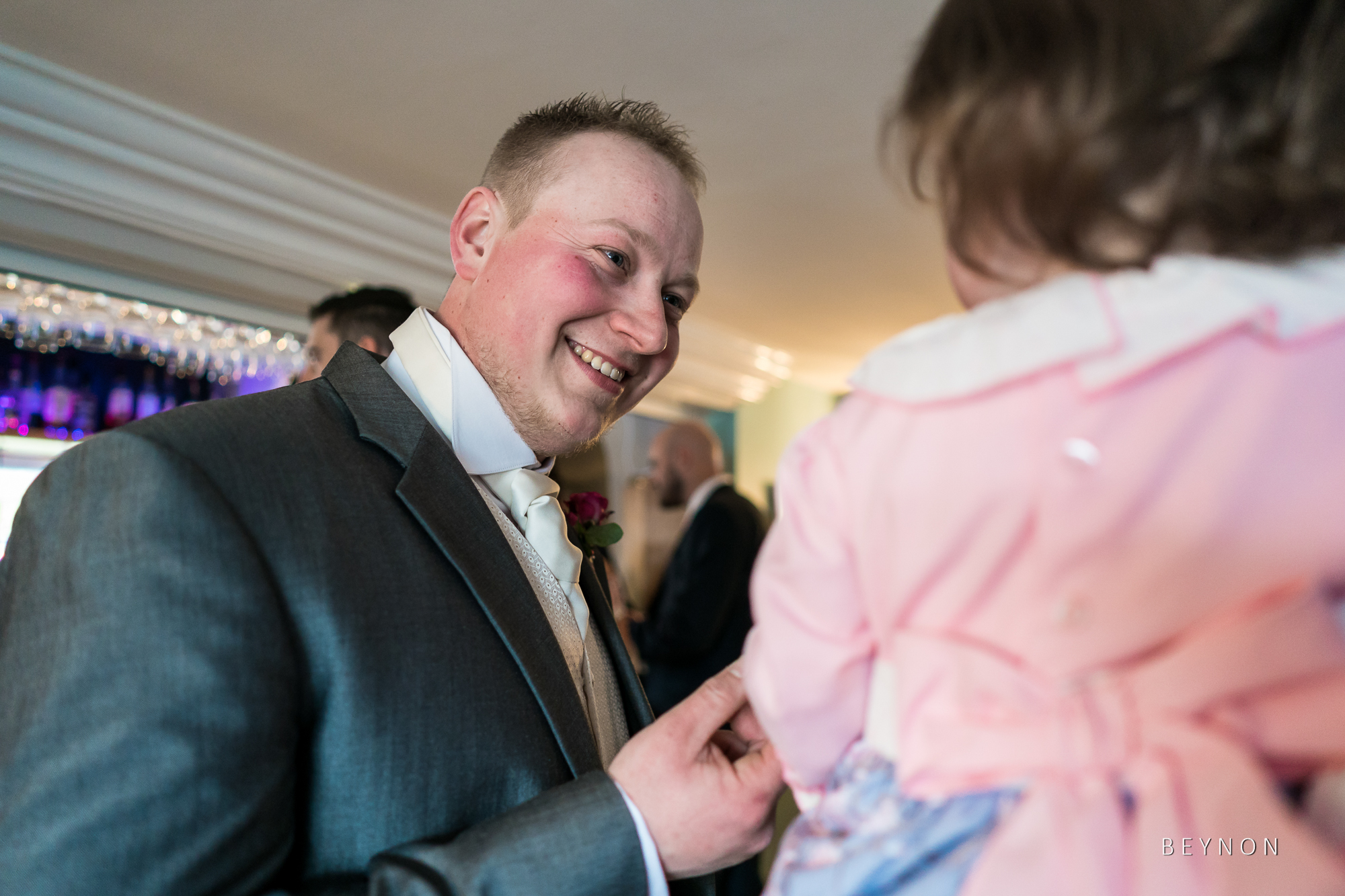 Groom smiles with child