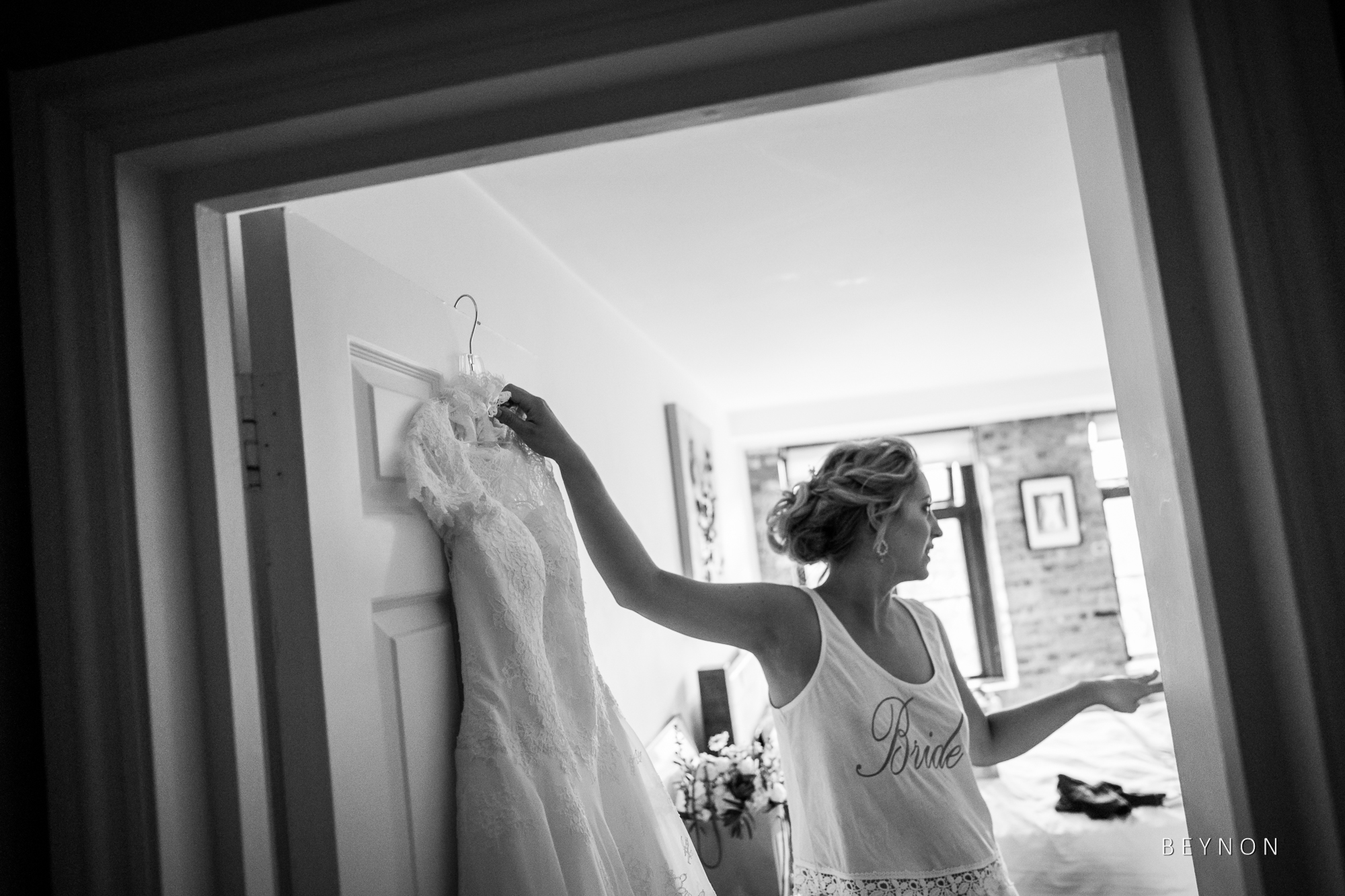 Bride reaches for her wedding dress