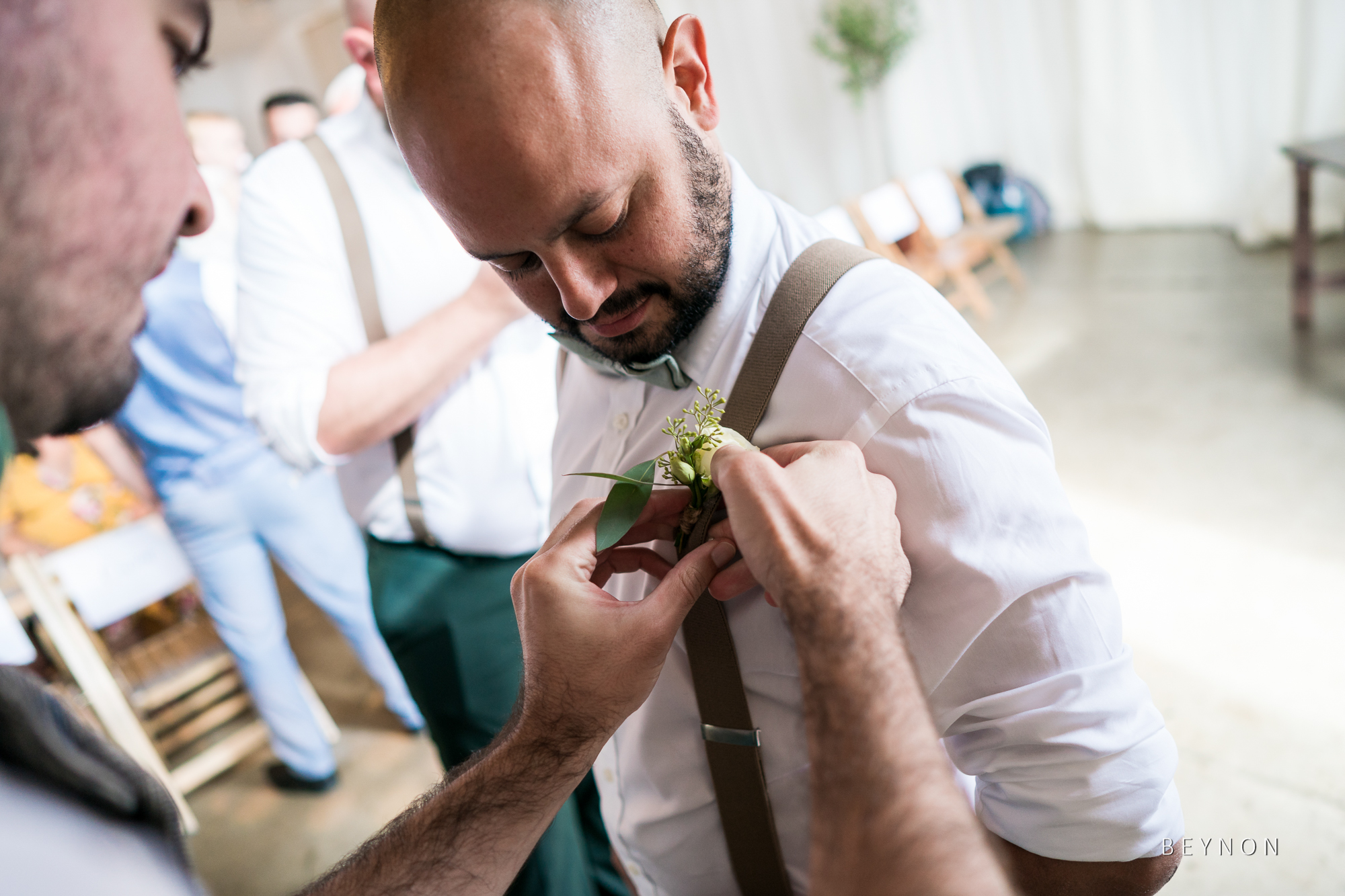 The Groom puts buttonhole on usher
