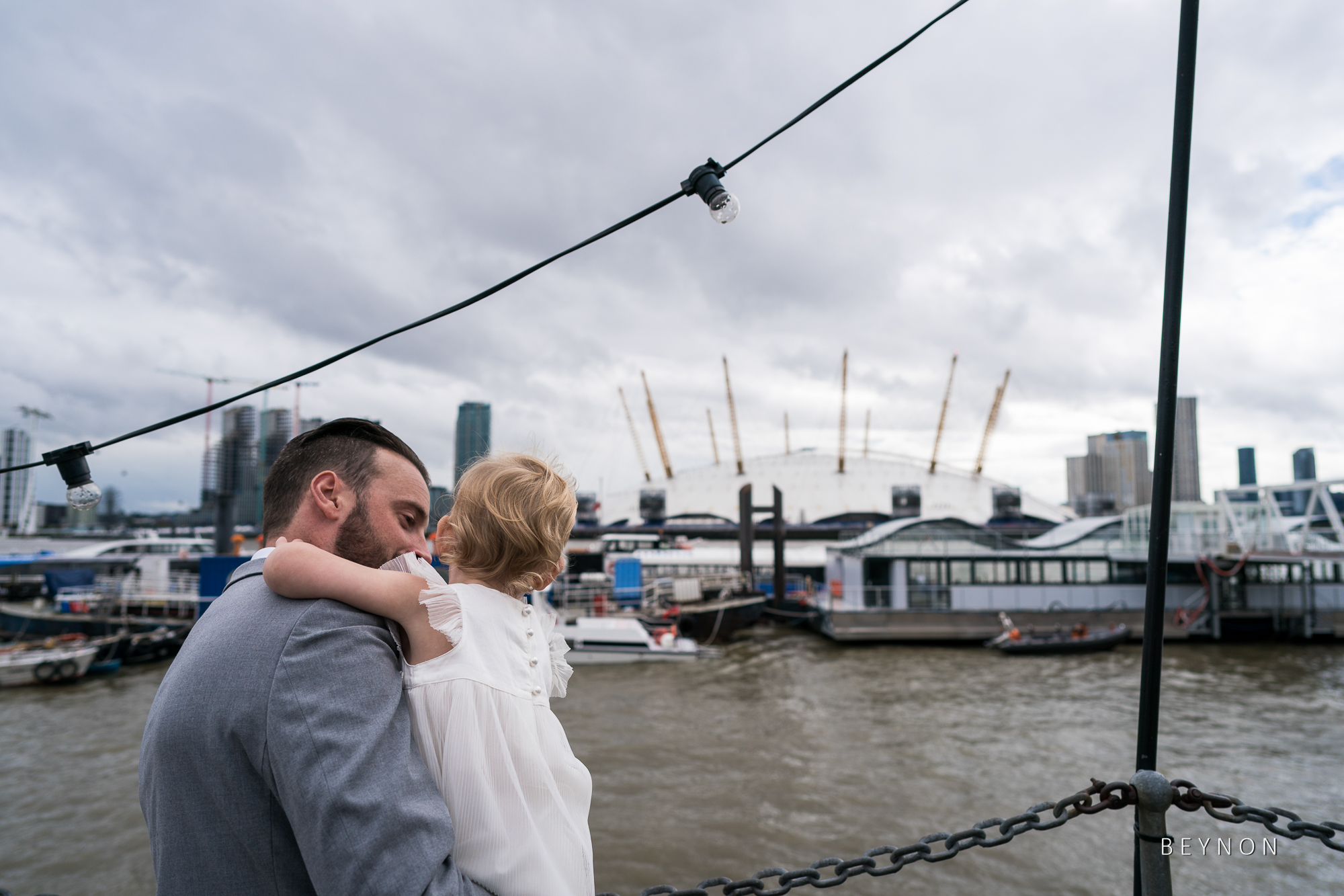 Wedding guests look out over the River Thames to the O2 arena
