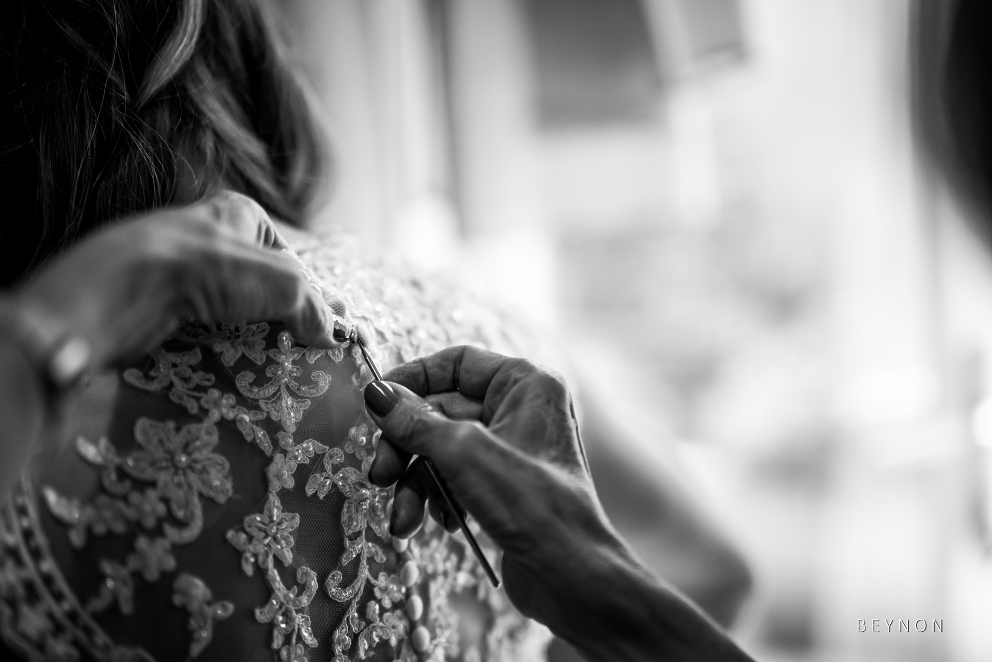 The mother of the Bride does the back of the wedding dress up