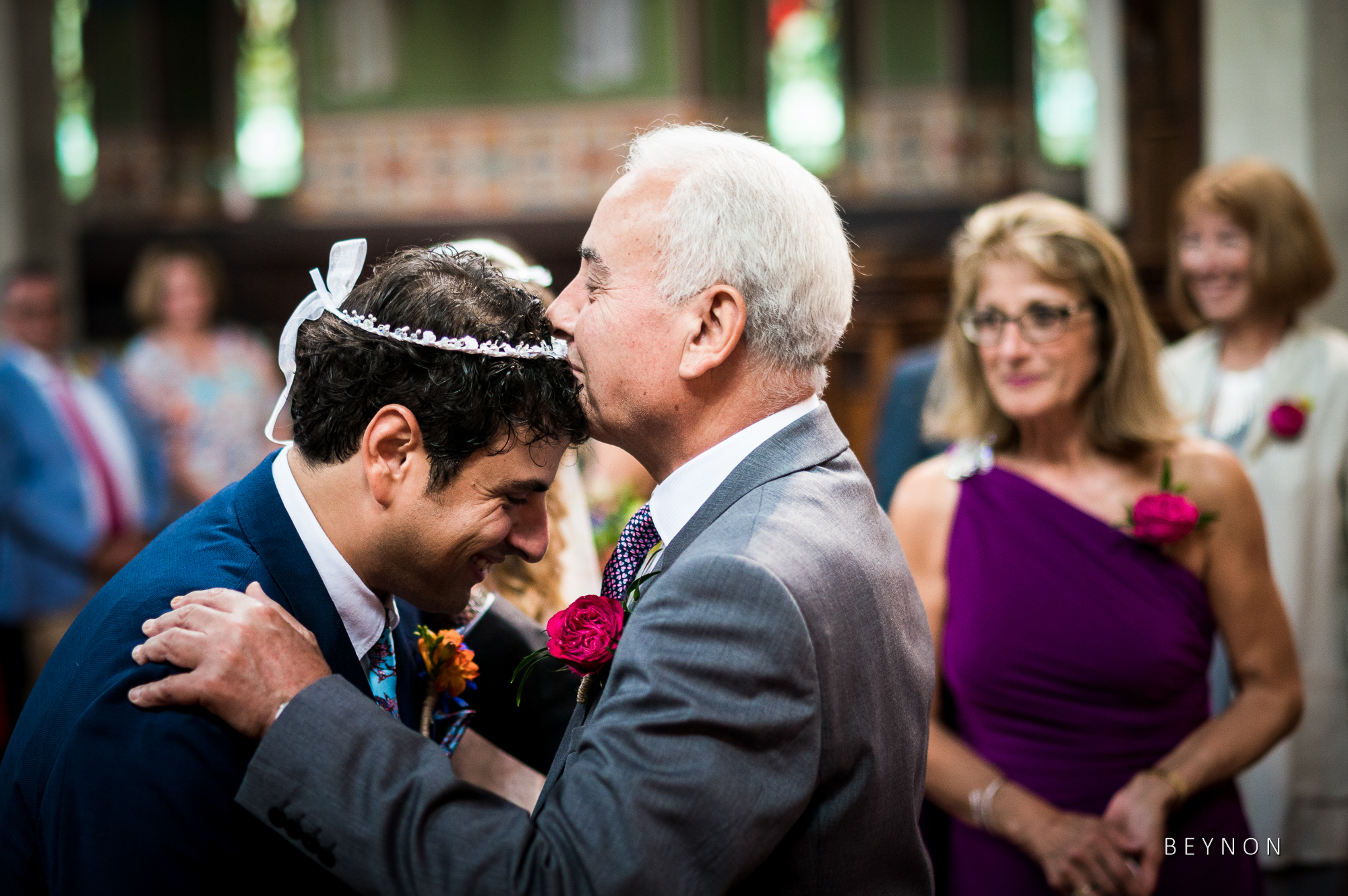 the father of the bride kisses the groom on the forehead