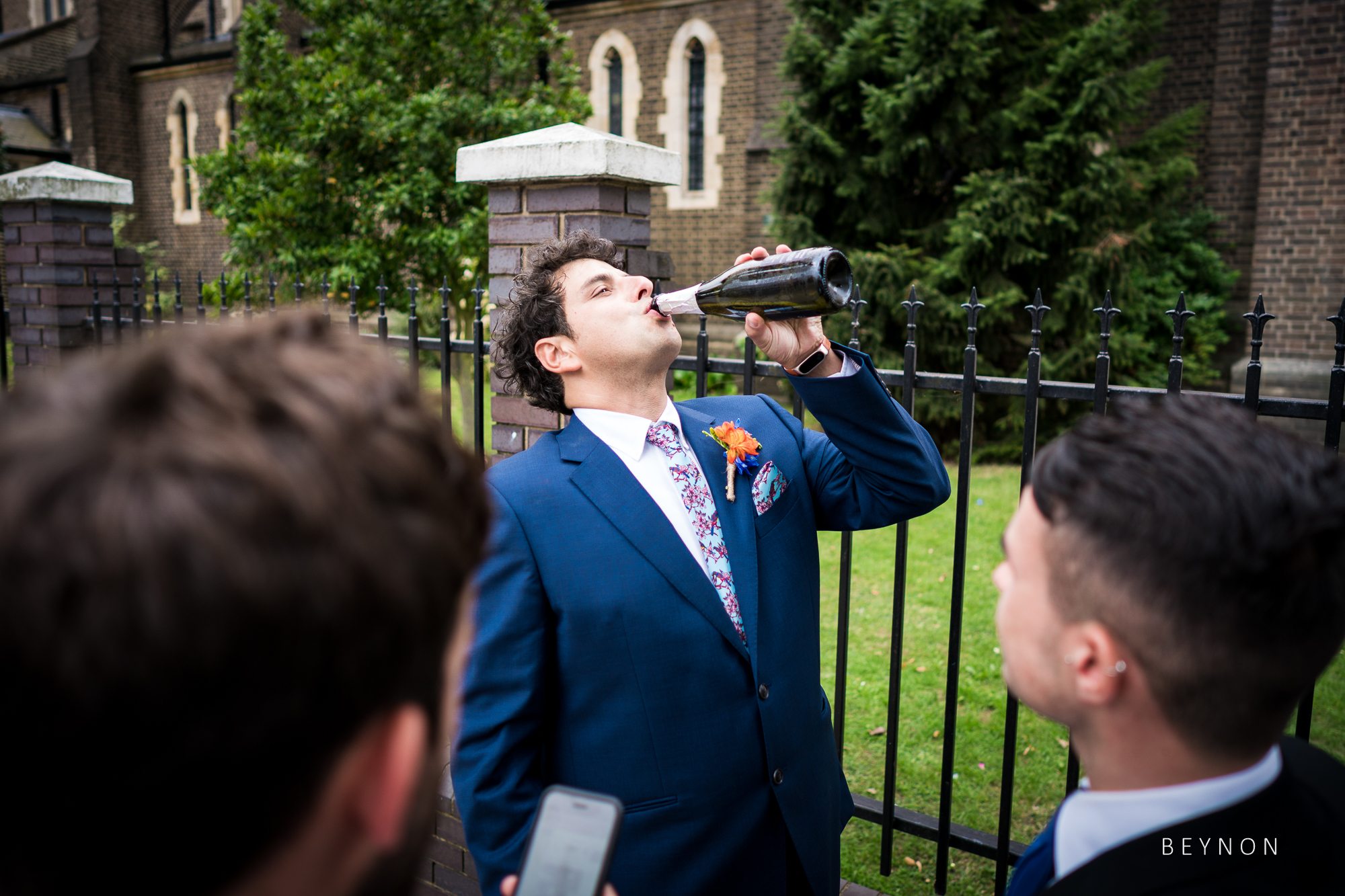The groom downs a bottle of wine.