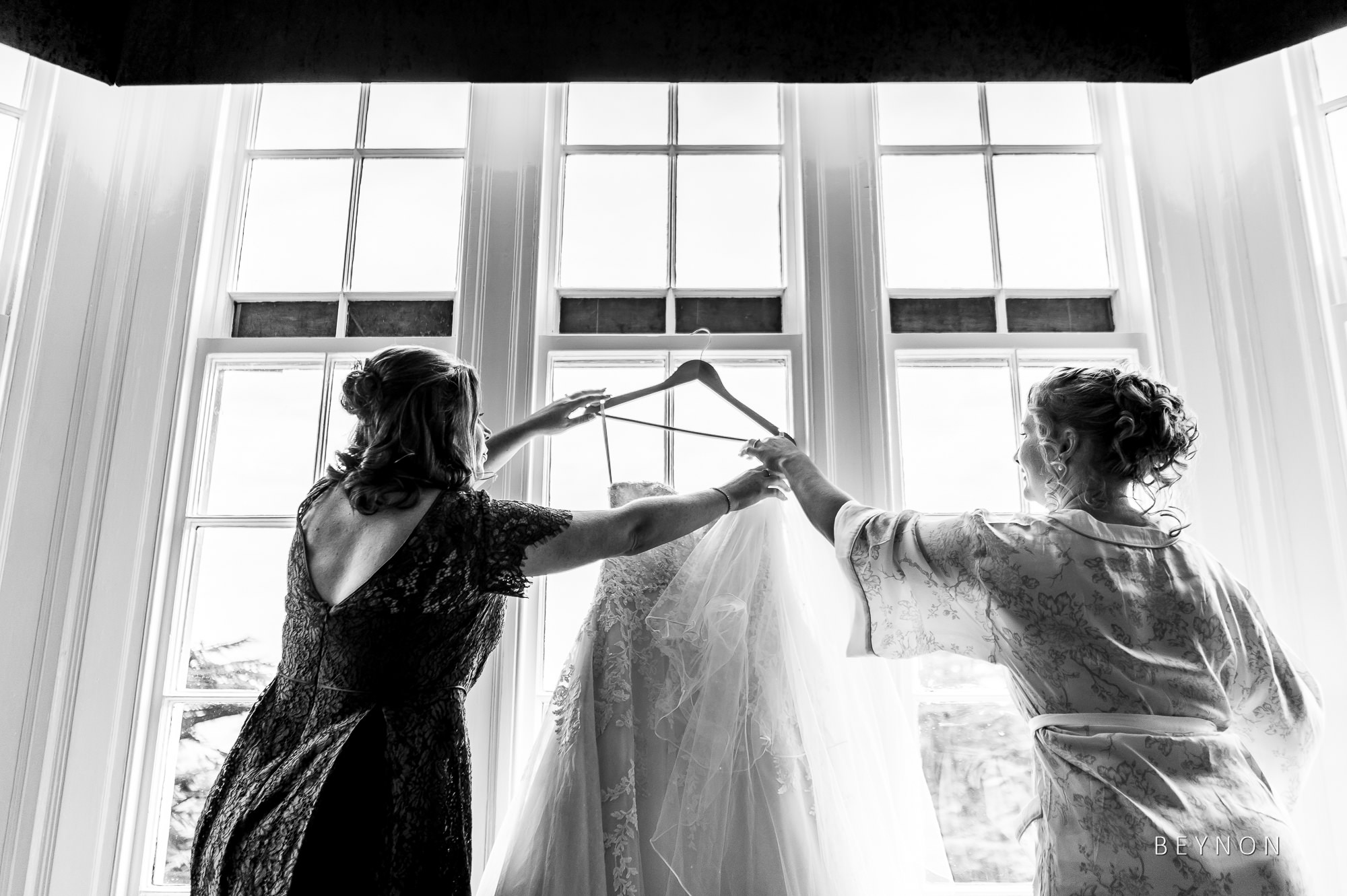 Bride and bridesmaid hold wedding dress