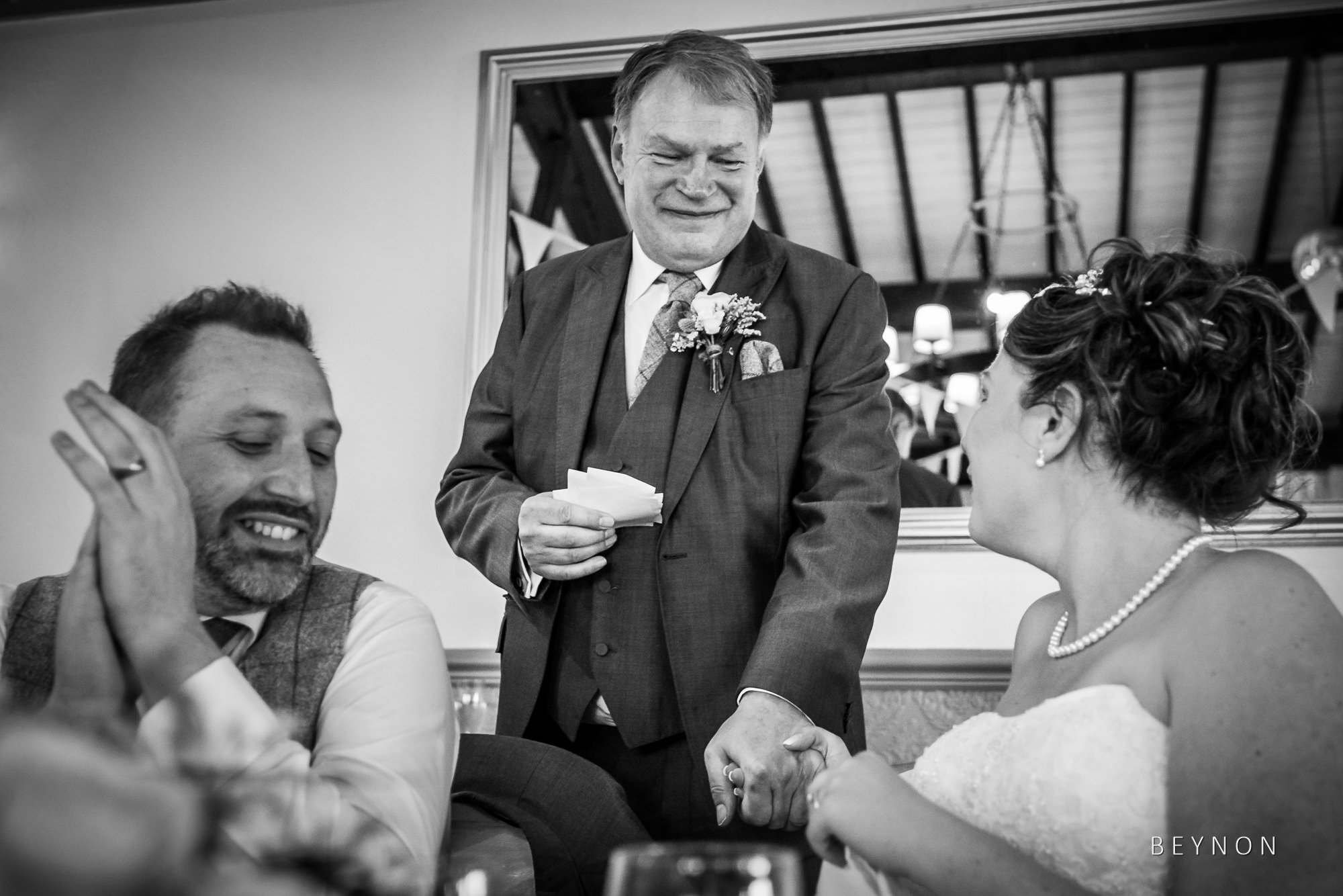 Dad and bride hold hands during speech