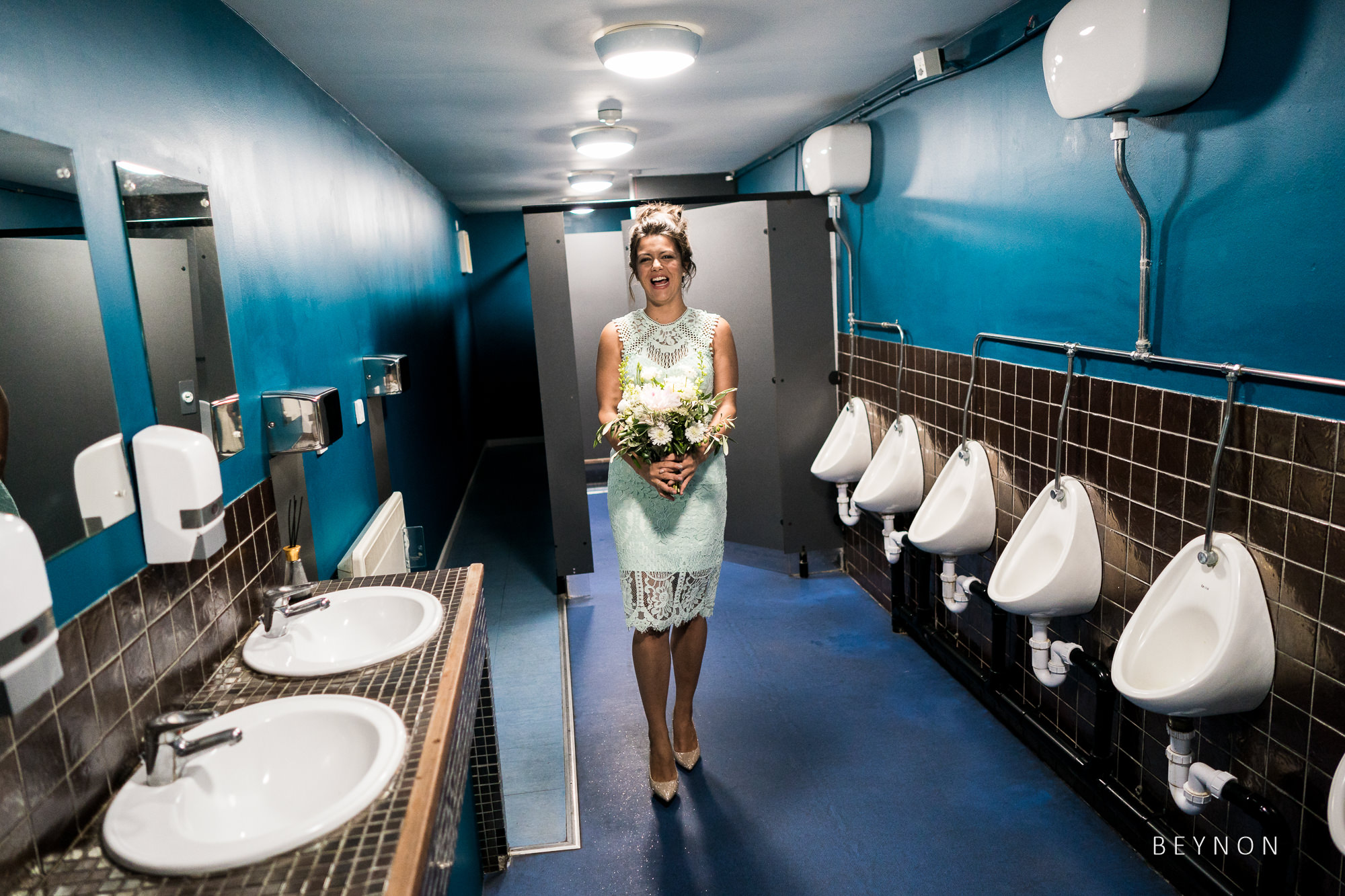Bridesmaid practices her walk in the men's toilets