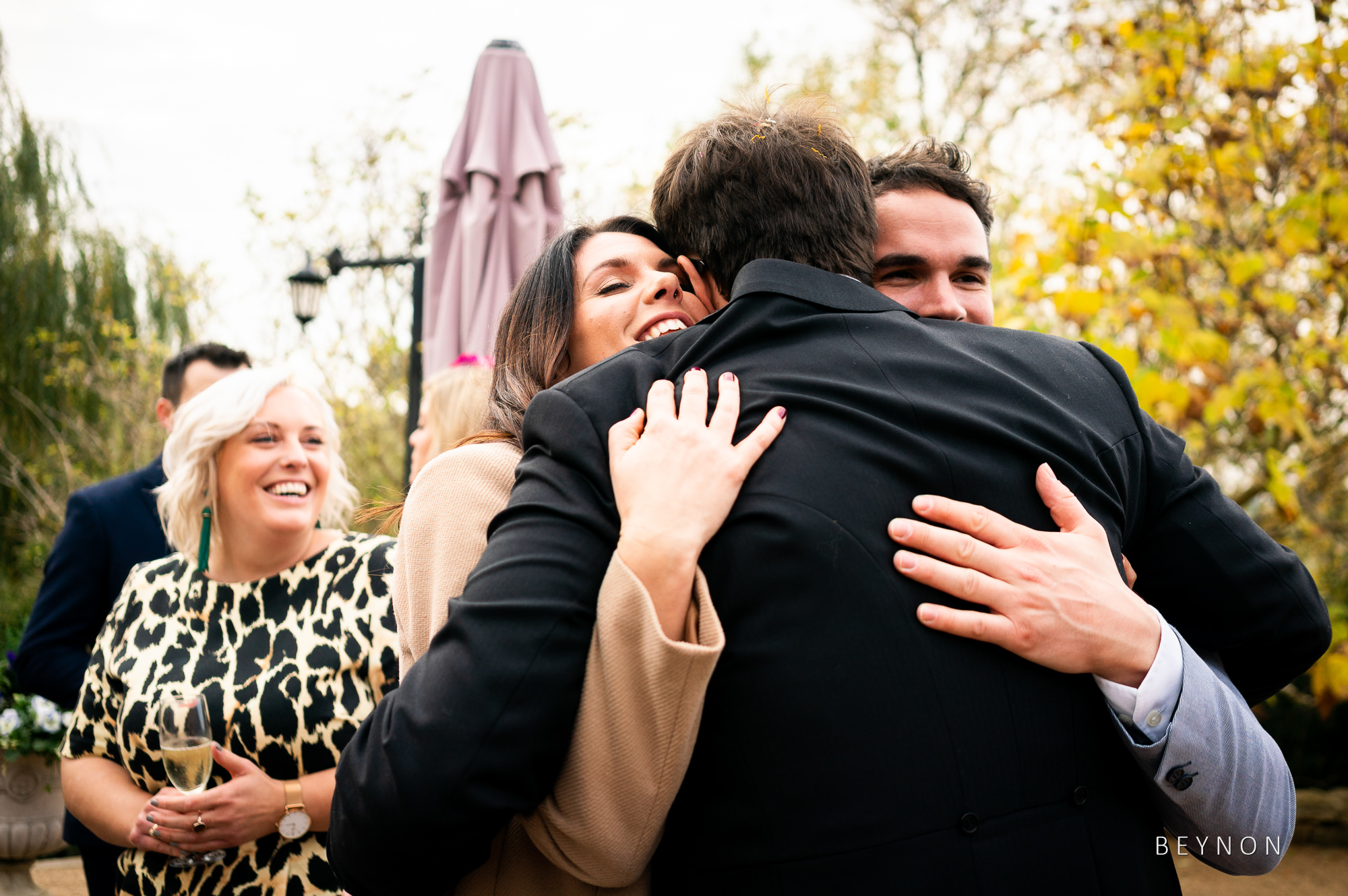 Groom double hugs two guests