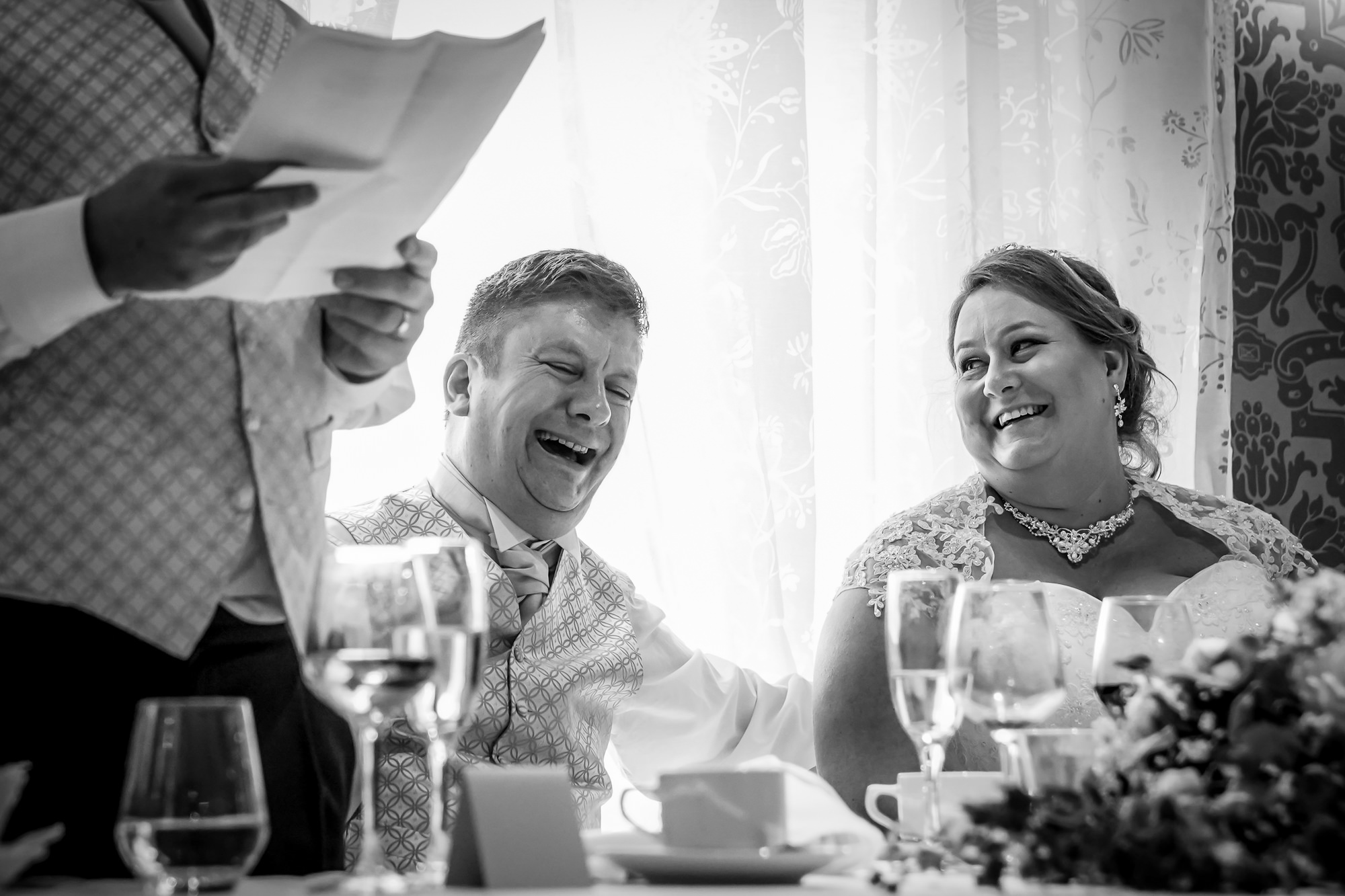 The Bride & Groom laugh during the speeches