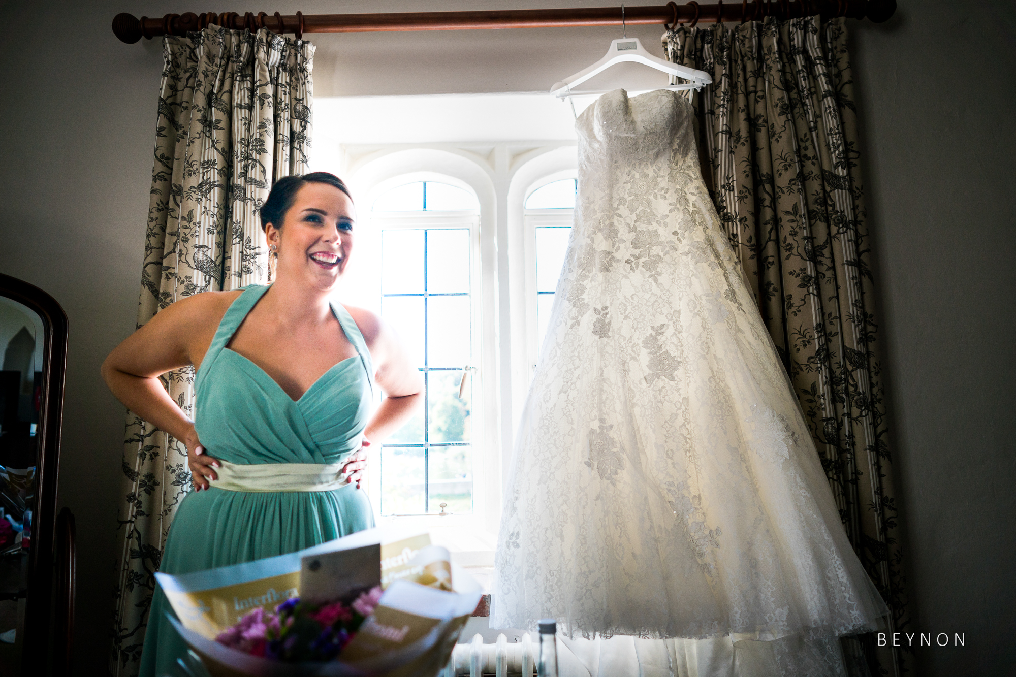 Bridesmaid stands next to wedding dress