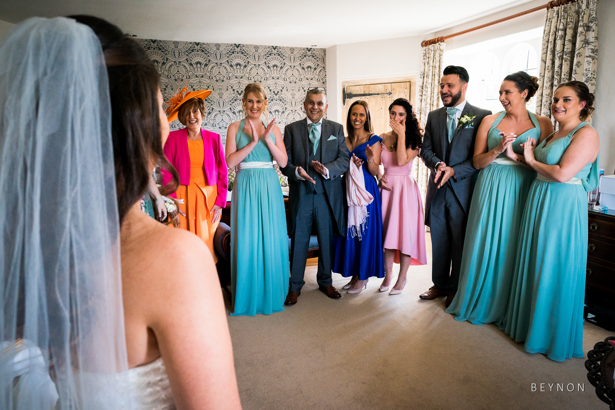Bride shows off dress to bridal party