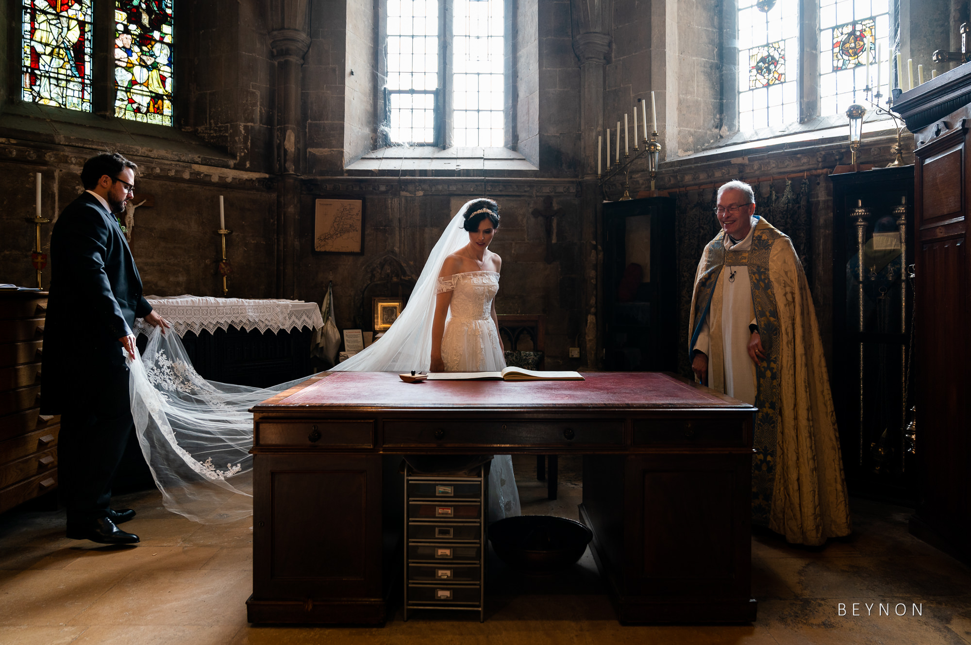 Bride sits to sign the registar