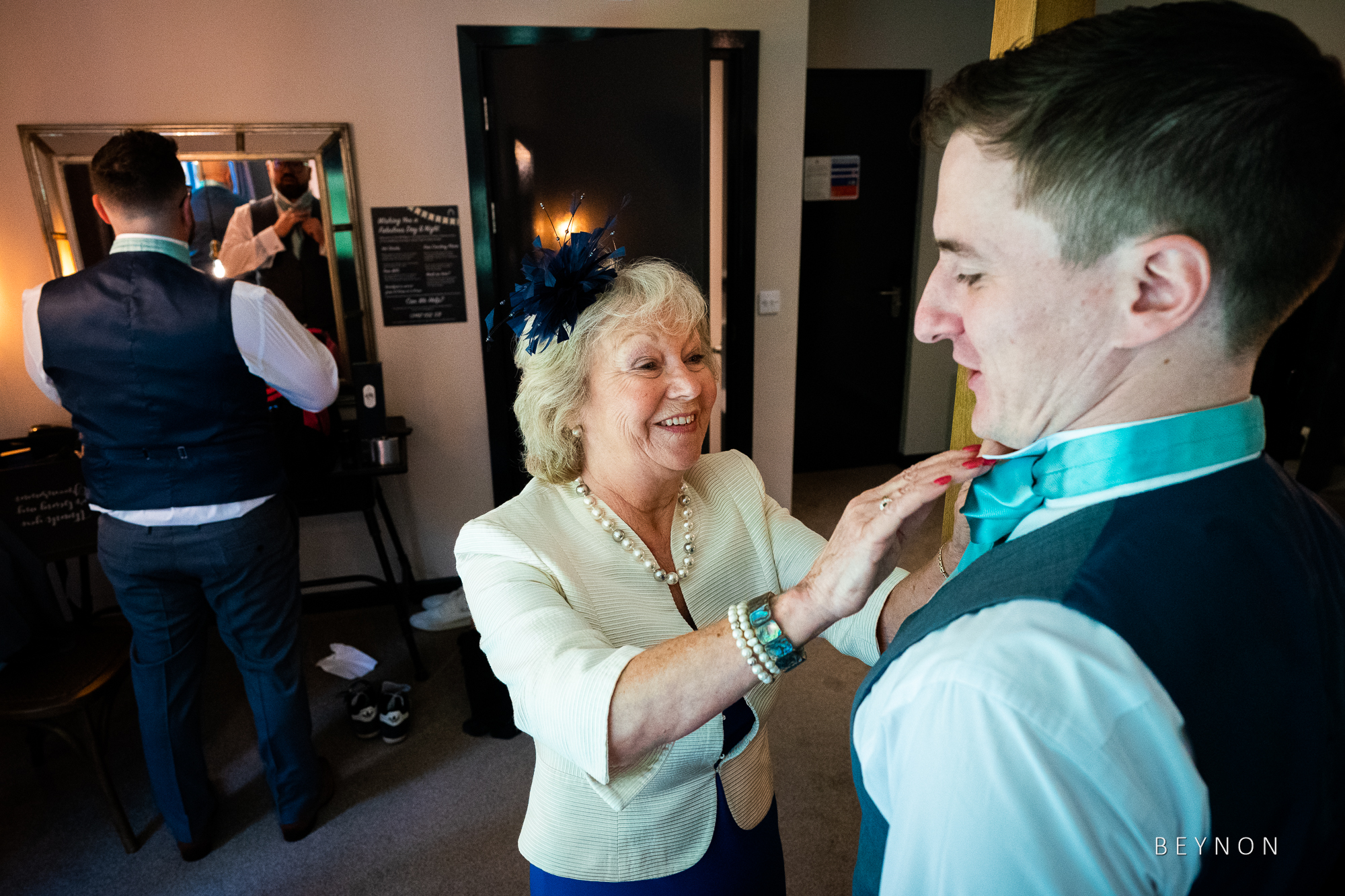 Guest helps with groomsman's cravat