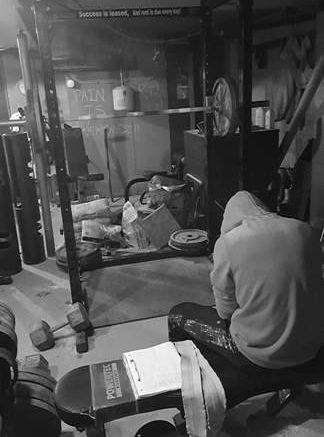 World Champion powerlifter Casey Walker takes a moment between lifts in his garage gym.