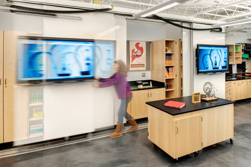 White boards and interactive screens are mounted on rolling wall panels that facilitate a greater variety of furniture configuration.