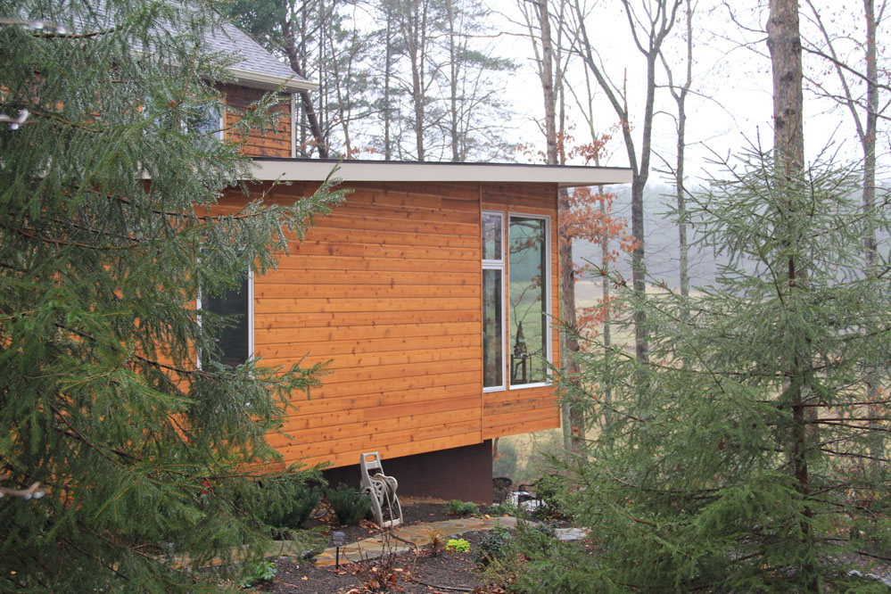 Young Hemlock trees frame the addition which is clad in shiplapped cedar siding.