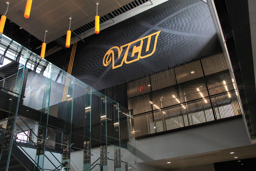 Clerestories provide abundant light to the rich palette of steel, glass, and wood in the building lobby.  Large-format graphics reinforce the VCU brand throughout the facility.