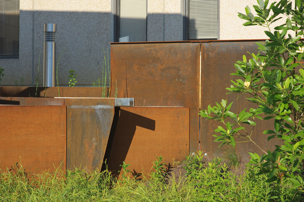 A custom-detailed scupper conveys plaza stormwater beyond the new weathering steel alloy walls and into a biofilter planted with Sweetbay Magnolia and other native Virginia plants.