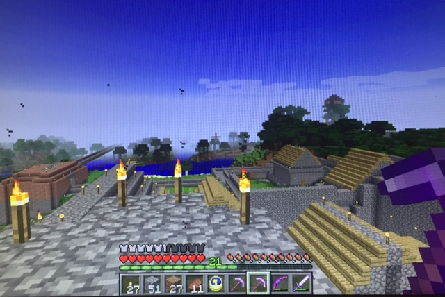Everything the light touches... the view of some of my castle farm in Minecraft. To the left, a train station. to the right is where I keep the farm animals.