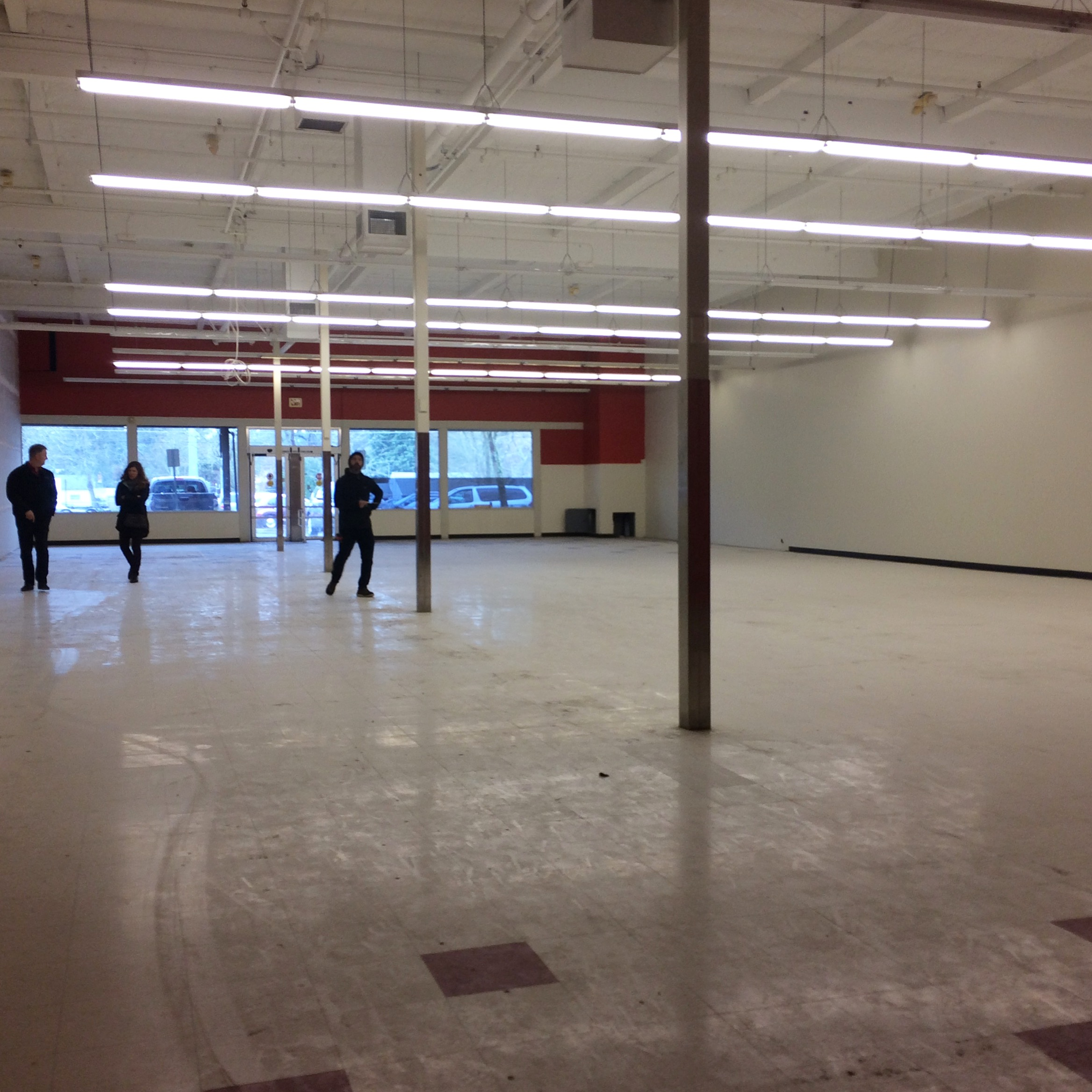Back to front view of our new space in Milwaukie. *Image shows a large commercial space with dusty tile flooring, in the back are large windows looking out to a parking lot, and a few people examining the room*