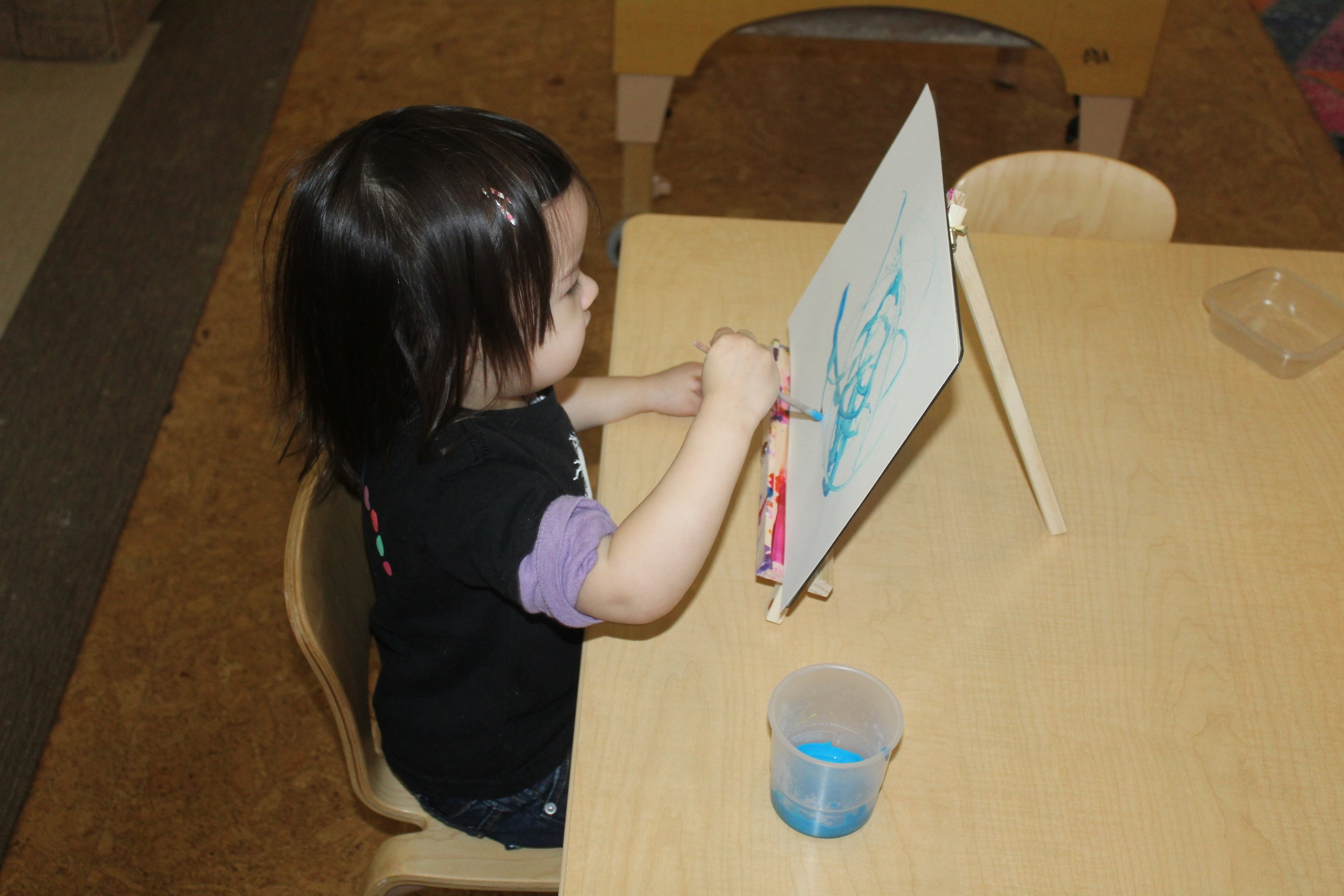 The children have been enjoying painting at the small easel.They are exploring and discovering new ways to move their arms to create different brushstrokes. I enjoy observing as they maneuver the paintbrush to create an art piece. Each brushstroke is dissimilar from one another. As they move their hand, they create delicate lines; some represent a person or an object.