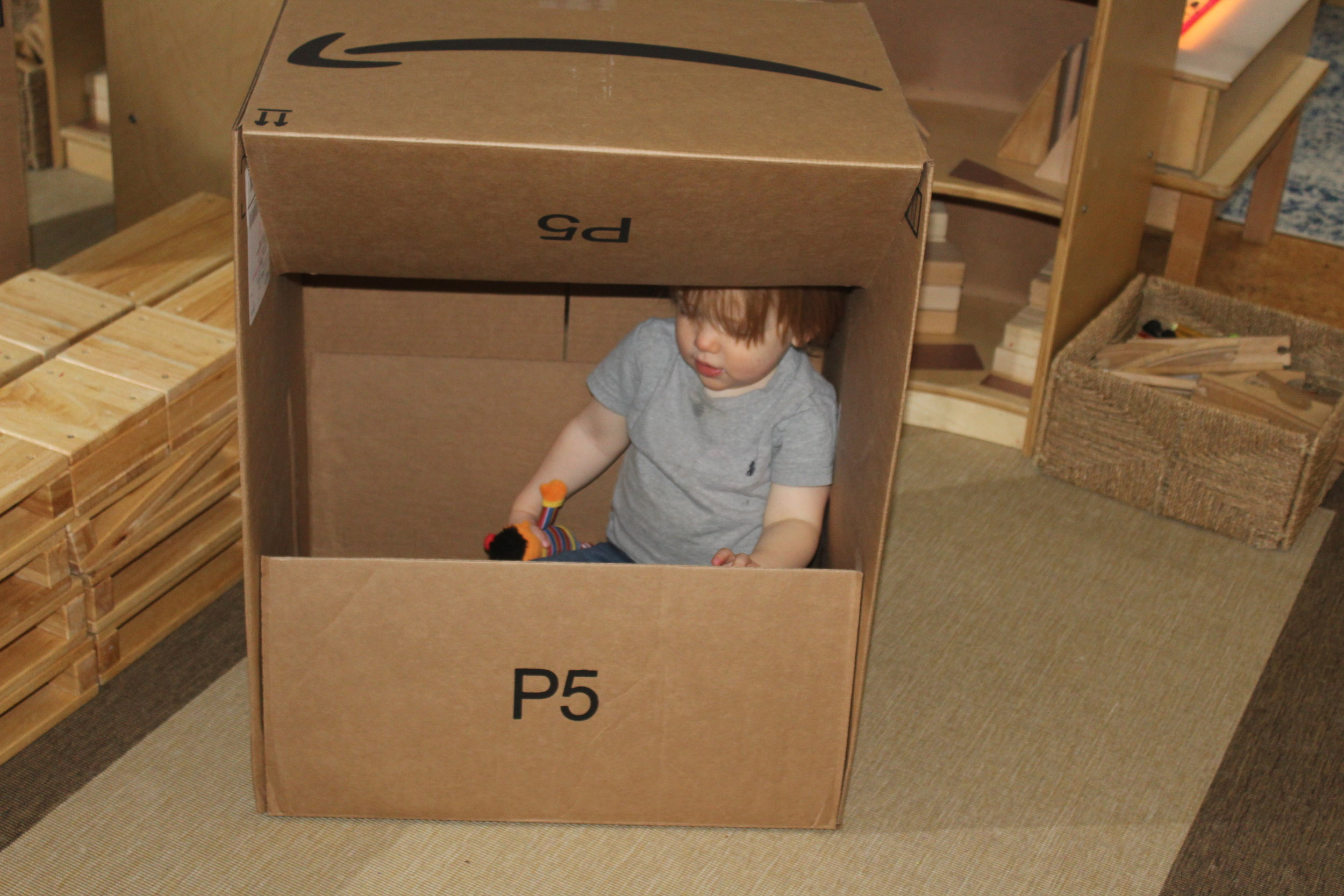Toddlers are learning to understand their own space. Children are constantly testing their body; they crawl in, around, over, and under things. The first thing toddlers do when they see a cardboard box is to try to get in it. As they explore getting into the box, they are discovering their body. Cardboard boxes are excellent tools for spatial exploration, and understanding their space.