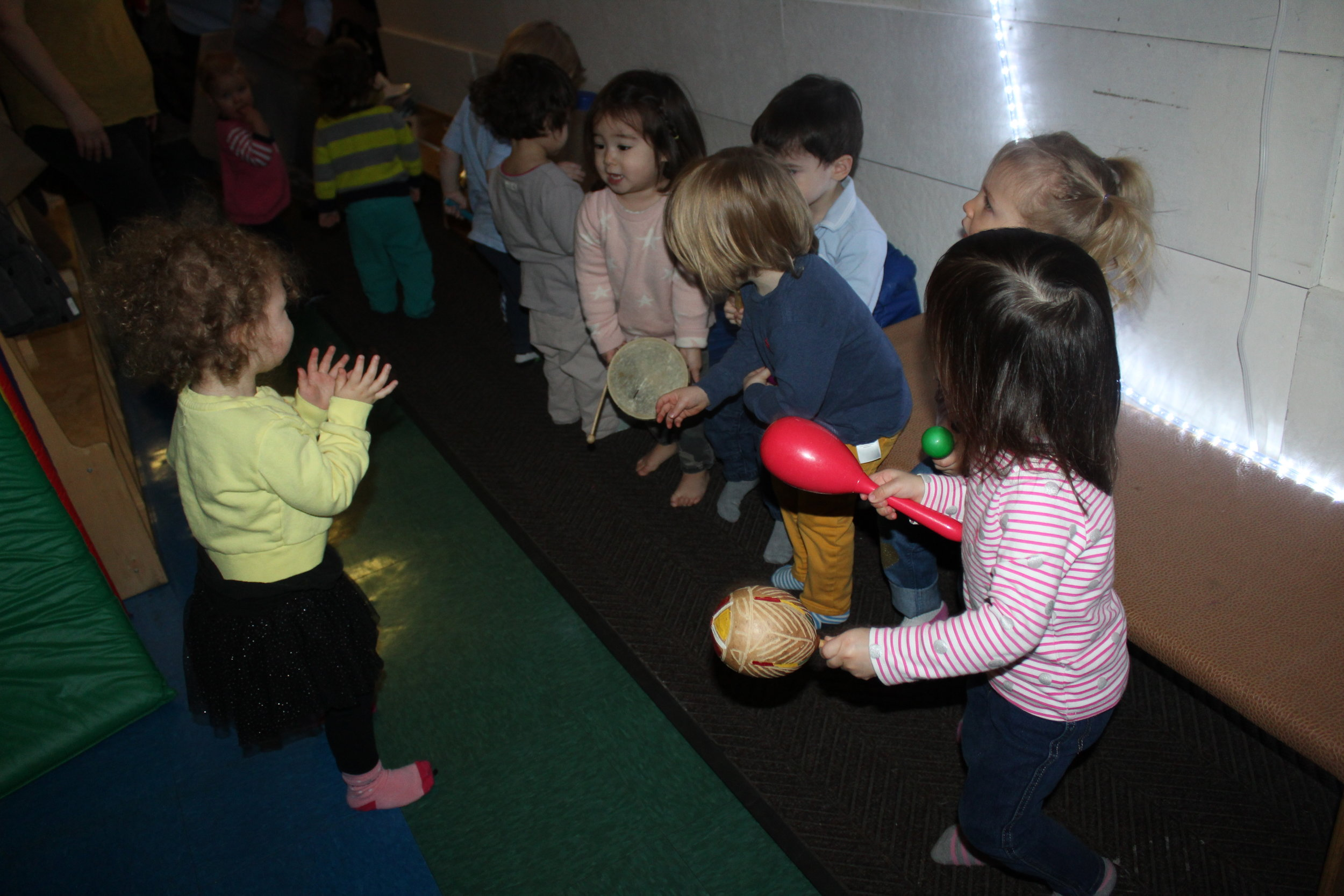 """Part of our curriculum is to provide music.The words and instruments are the special elements that make the music come alive. Children smile,jump,clap, and sway to the music they hear.These experiences promote the development of listening and language skills, motor skills, and creativity.  We visit the """"Music Wall"""" and the children explored and manipulated different instruments in the basket and the guitars displaying on the wall. As they played an instrument they sang ABC, Mr. Sun, and Twinkle Little Star to name a few.Music and movement contribute to children's overall development.Listening to and making music helps children's developing brain.As children learn words to songs, it makes them feel proud and able to participate in singing."""