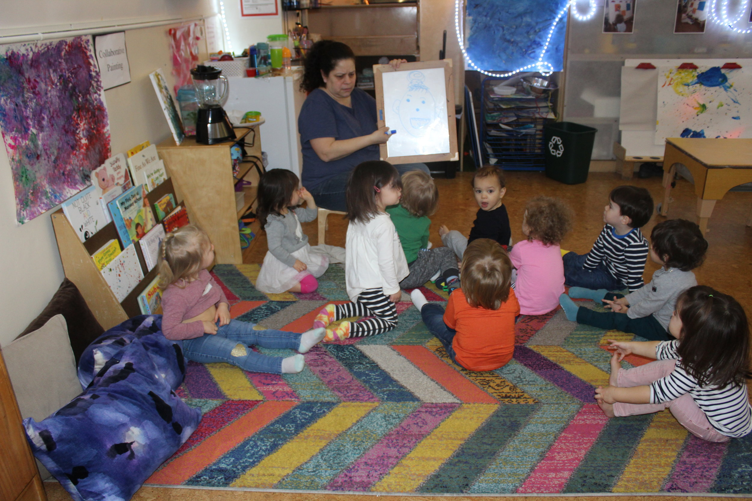 During circle time, Ms. Janet drew a self-portrait of Ms. Sandra. She asked the children, What is Sandra missing? All the children participated and articulated the different features until the self-portrait was completed. I don't see a resemblance; however, the children identified, recognized, and articulated the facial features.