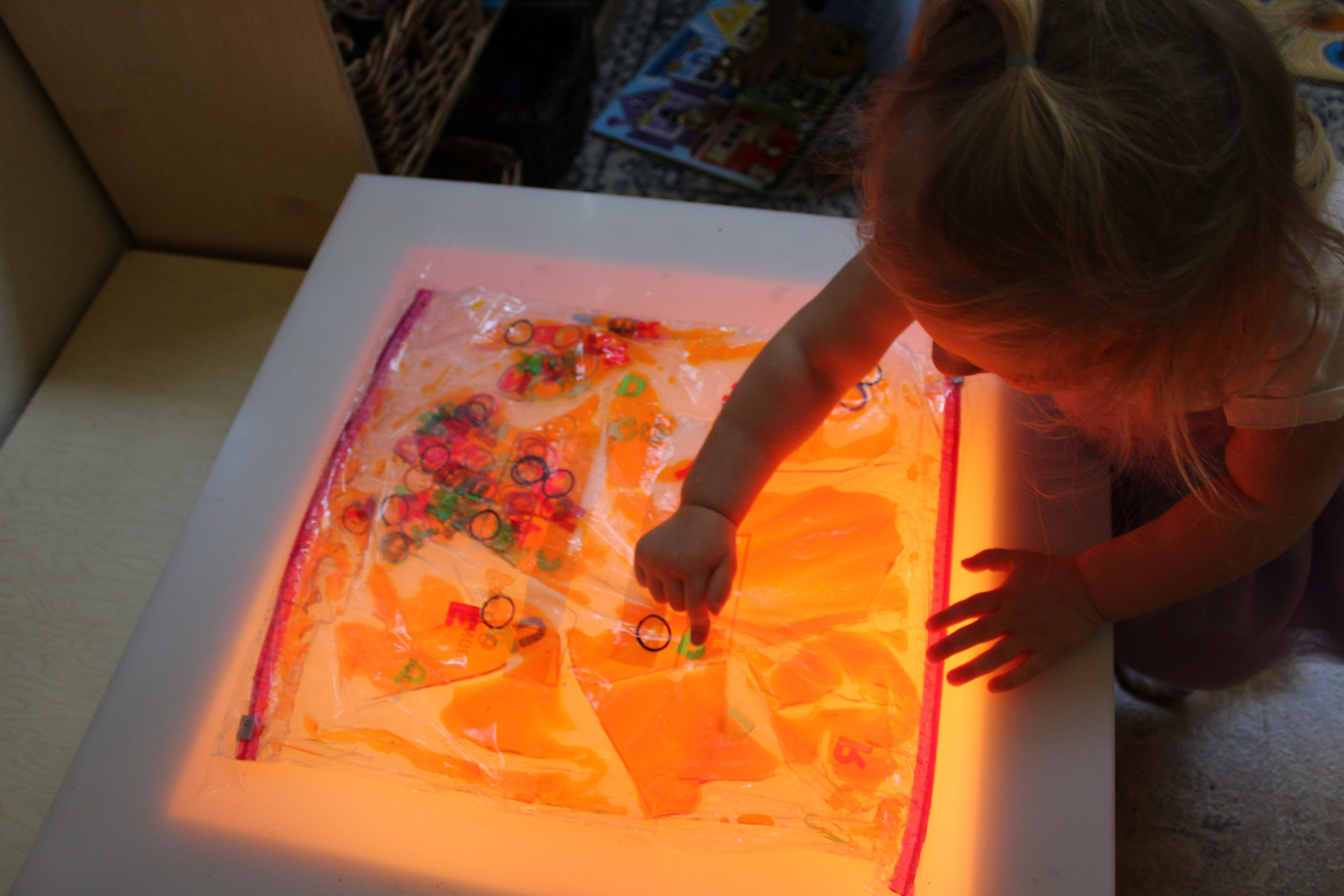 Sensory bags are inviting to toddlers. Sensory invitations to play is a delightful resource that encourages children to explore their sense of touch and sight.Madeline appears intrigued as she explores the sensory bag on the lightable. The bag contained water, baby oil, orange watercolor, colorful rubber bands and letters. She noticed how the watercolor moved as she touched and patted the Ziploc bag. Madeline used her fingertips to press each letter, and as she pushed, they moved. The movement encouraged her to touch other letters.