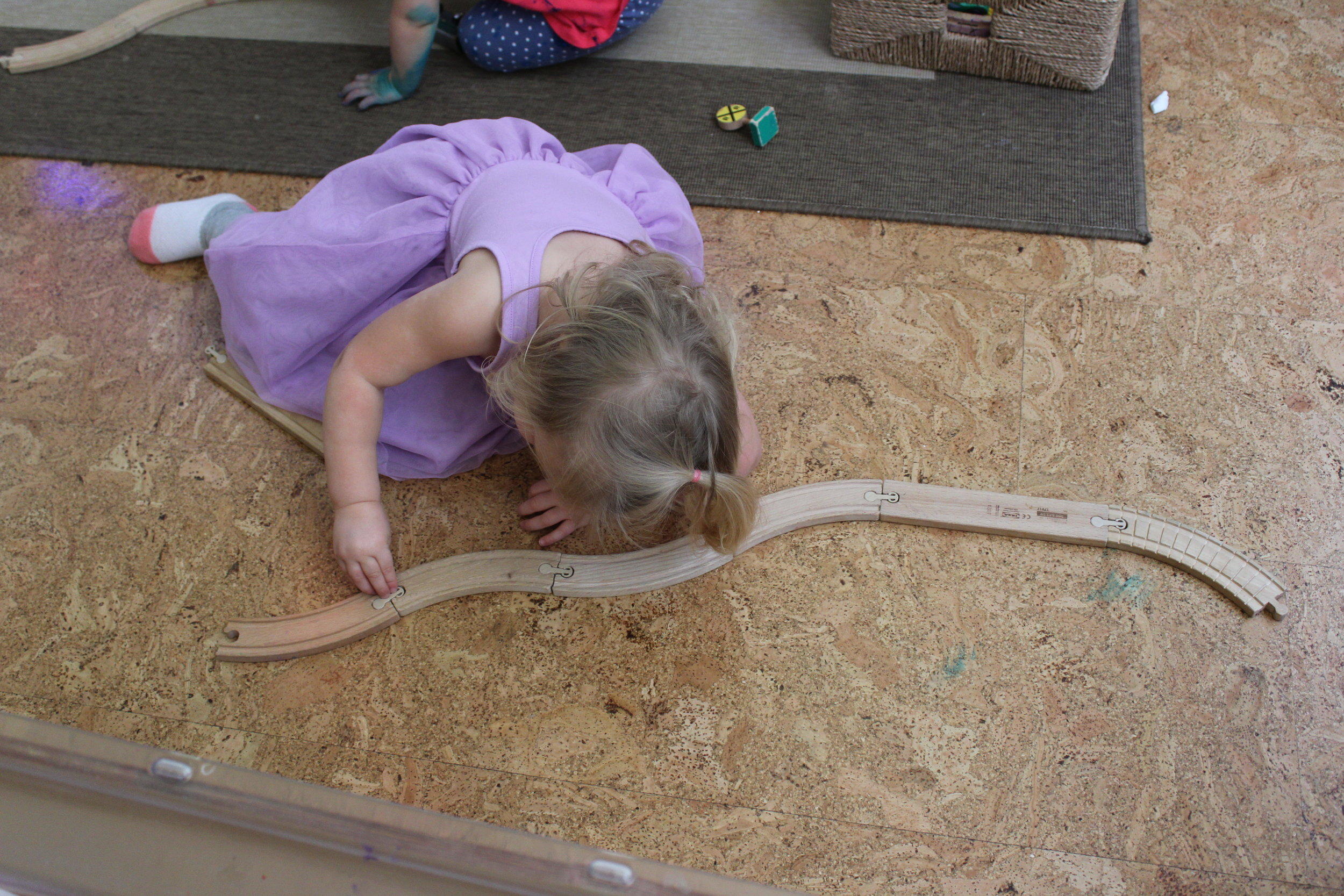 Train tracks are not only fun but developmentally appropriate for young toddlers. They are tools that help facilitate optimum child growth and development. Each piece stimulates Madeline imagination and creativity. It also enhances problem-solving skills. Madeline created her own track configuration. She carefully chose and connected each track. She observed and focused on each track, making sure it fits.