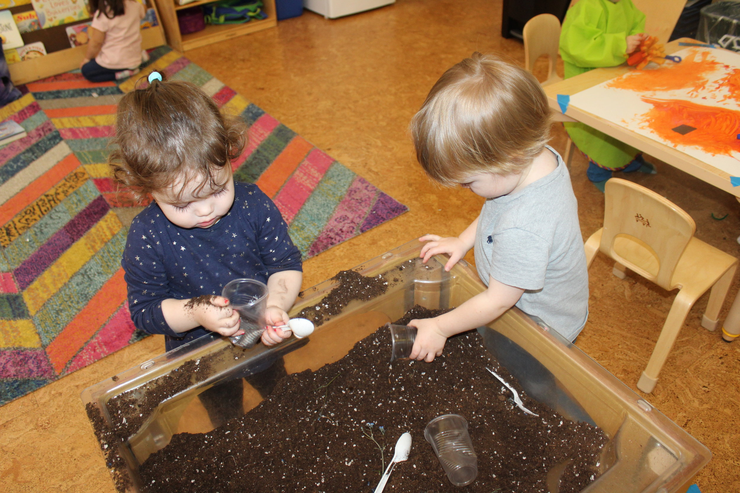 The children were excited to explore soil! The soil is one of the natural element for planting. They squeezed, touched,  and clutched some in their hands to pour it into a cup. They scooped and emptied small cups. We also included some props in the soil, to make the exploration fun, interesting and realistic (insects and branches).